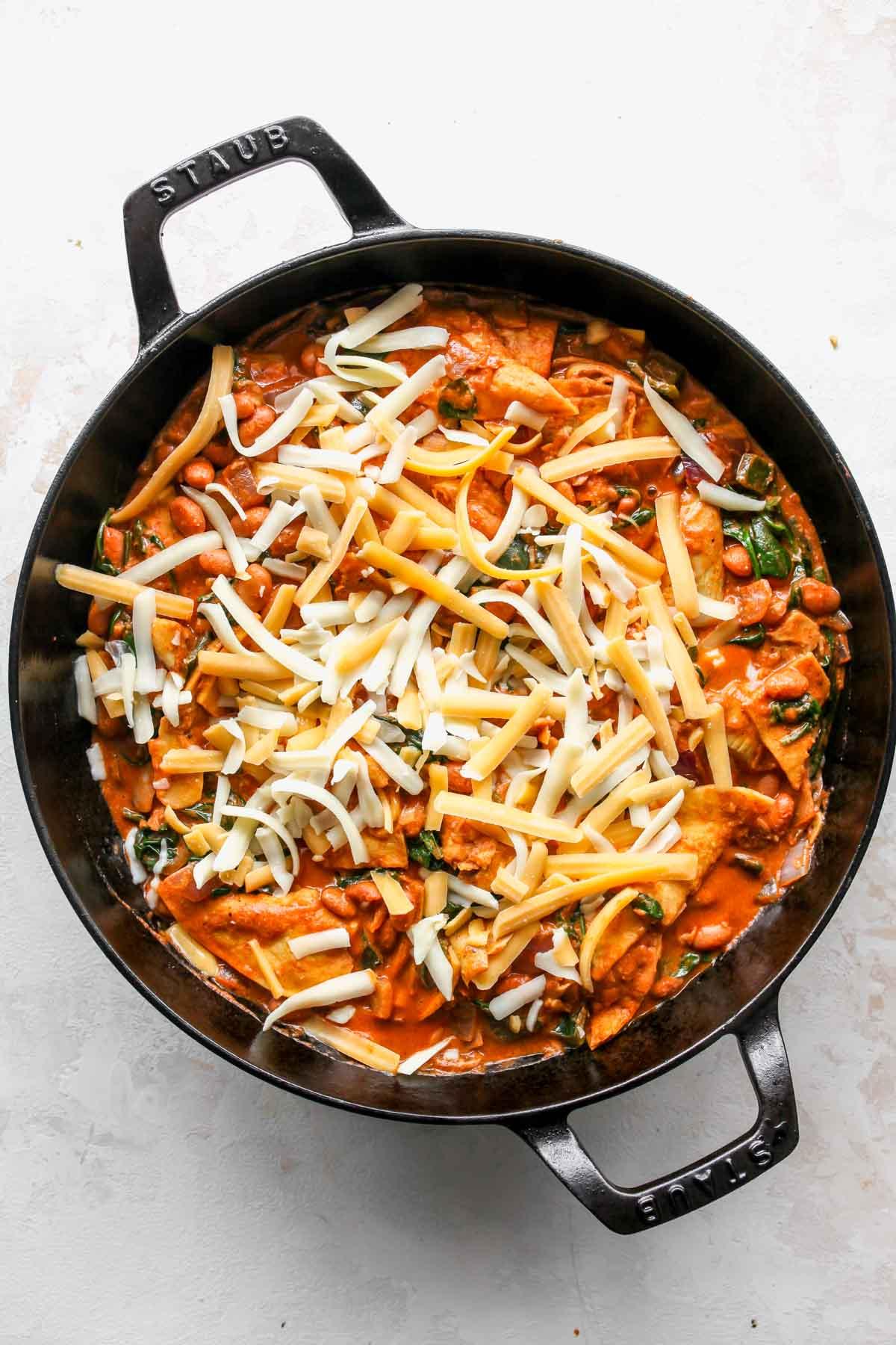 Sebzeler ve enchilada sosu karışımı üzerine serpilen peynir