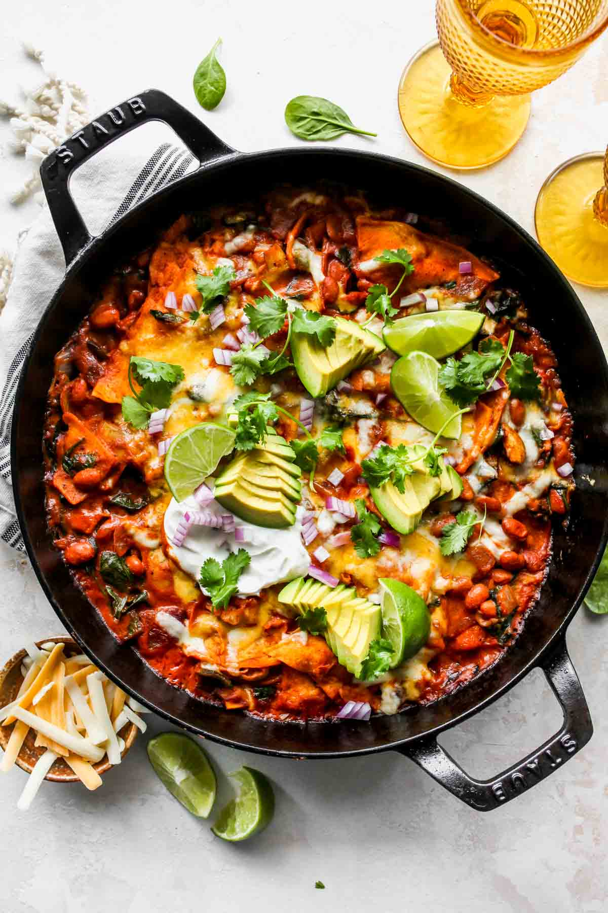 Skillet of vegetable enchiladas topped with avocado slices, cilantro, and lime wedges