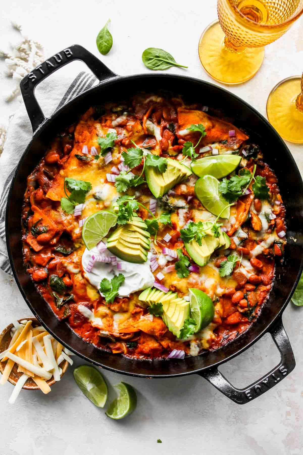 Avokado dilimleri, kişniş ve limon dilimleri ile tepesinde sebze enchiladas tavası