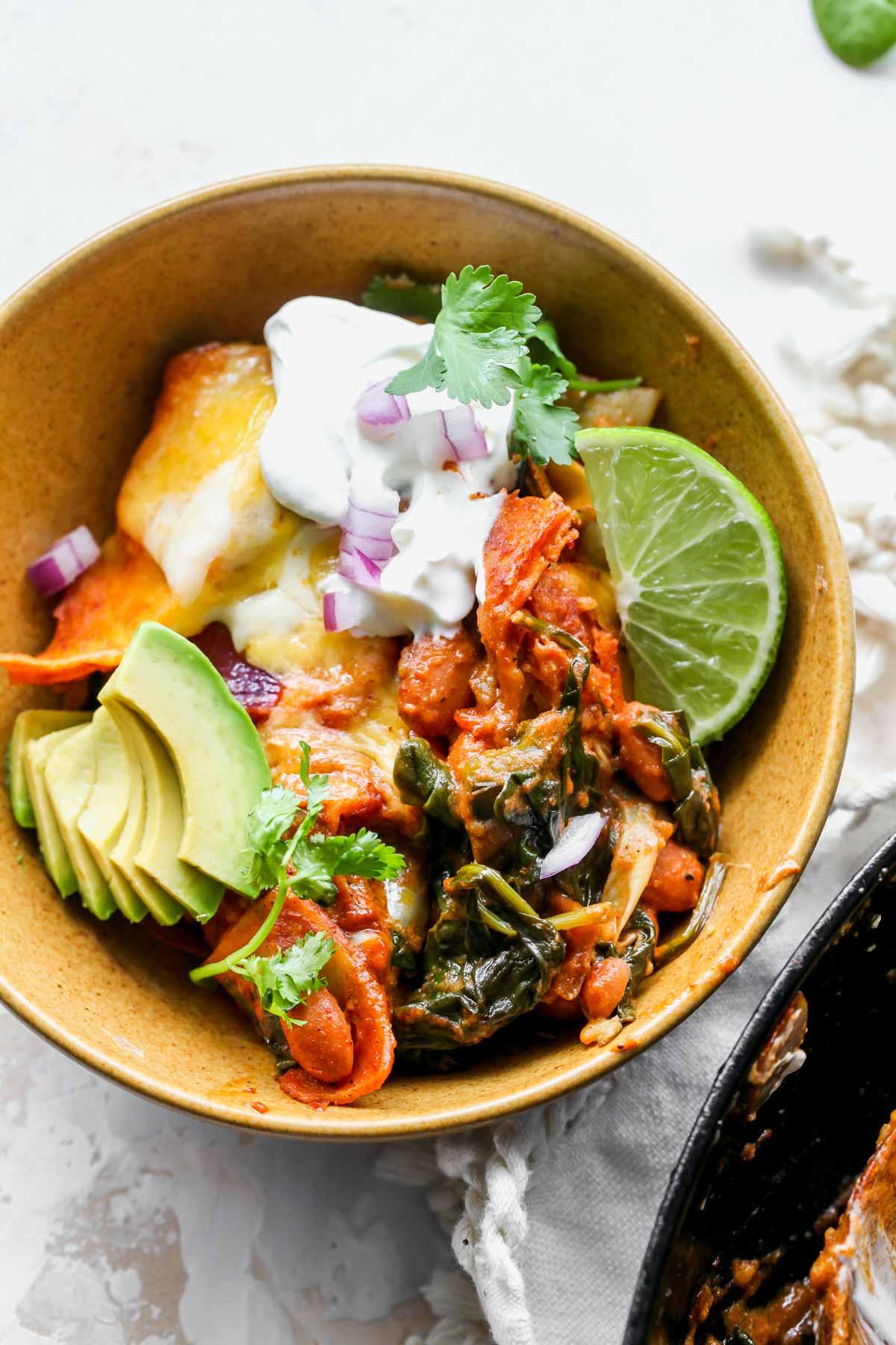Ekşi krema ve avokado ile süslenmiş altın bir kapta ıspanak ve enginar enchiladas tek porsiyon