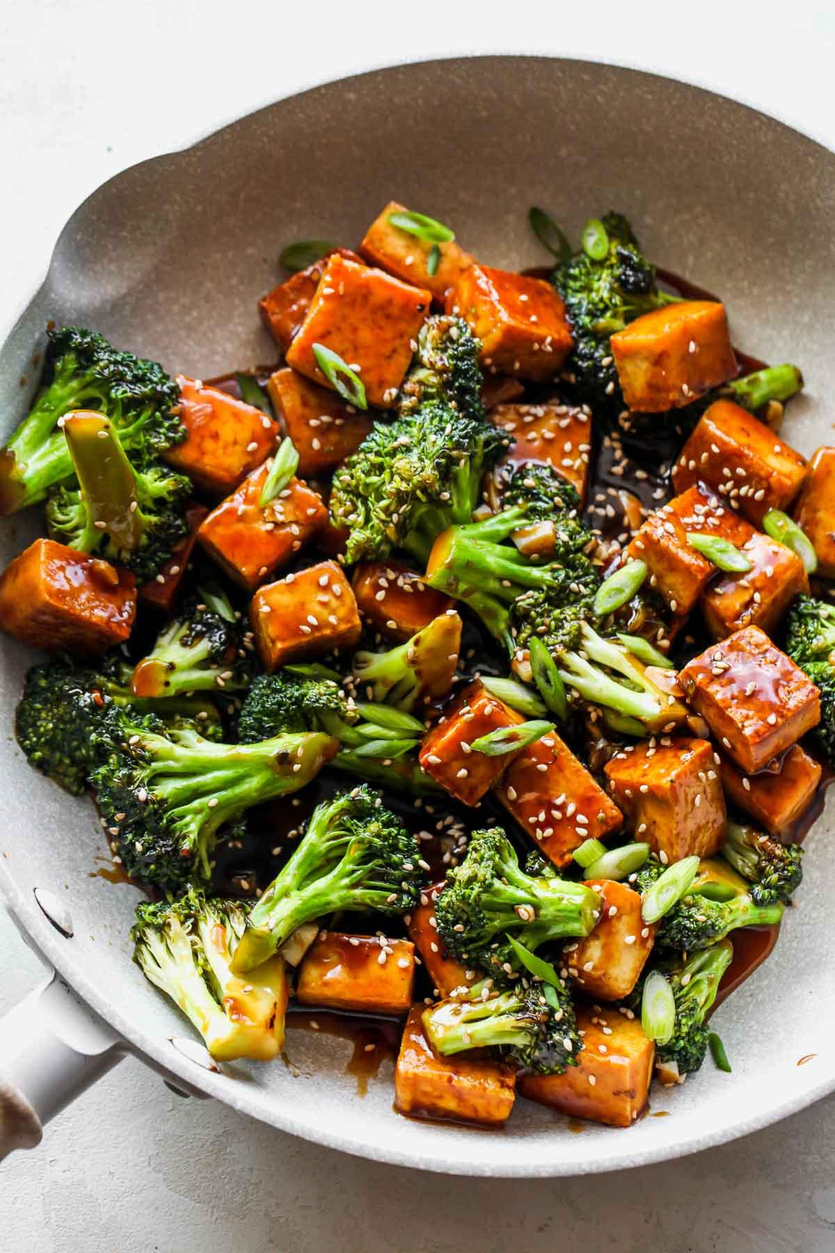 Teriyaki tofu and broccoli simmering in a white skillet