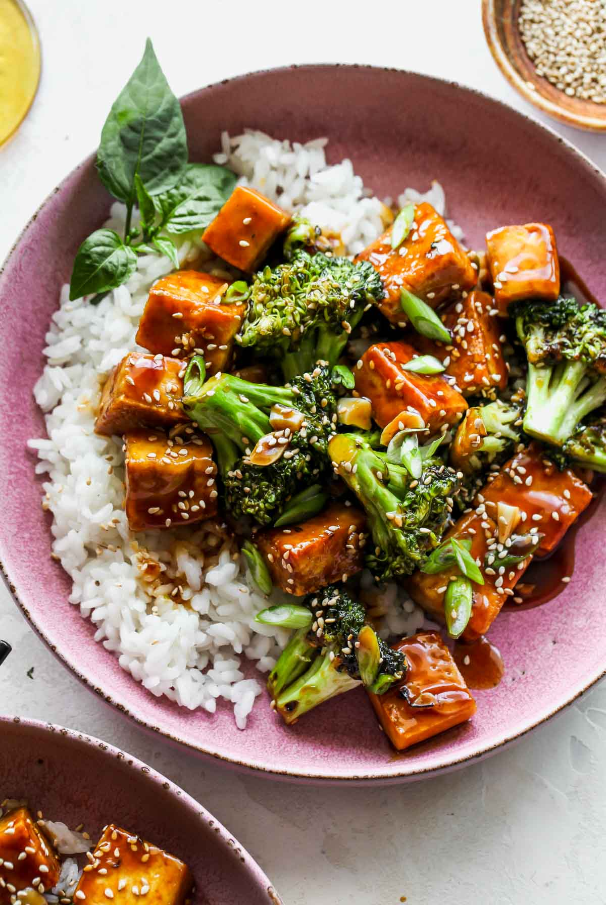 Finished recipe in a pink bowl topped with teriyaki sauce