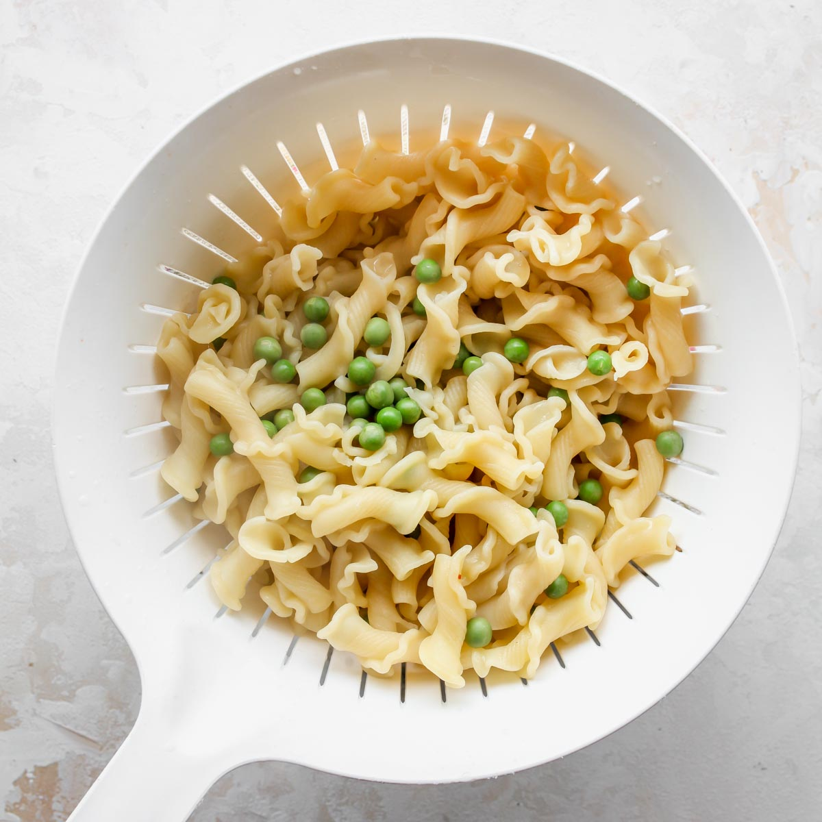 Cooked pasta noodles and green peas in a strainer