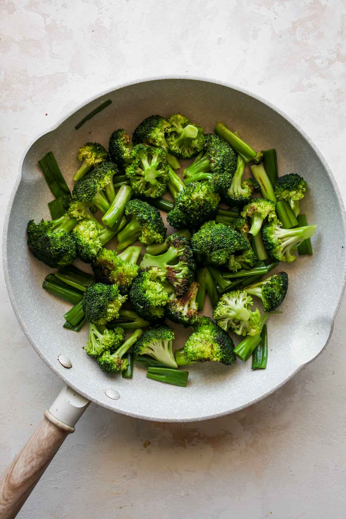 Broccoli florets and green onion being sautéed in a white skillet