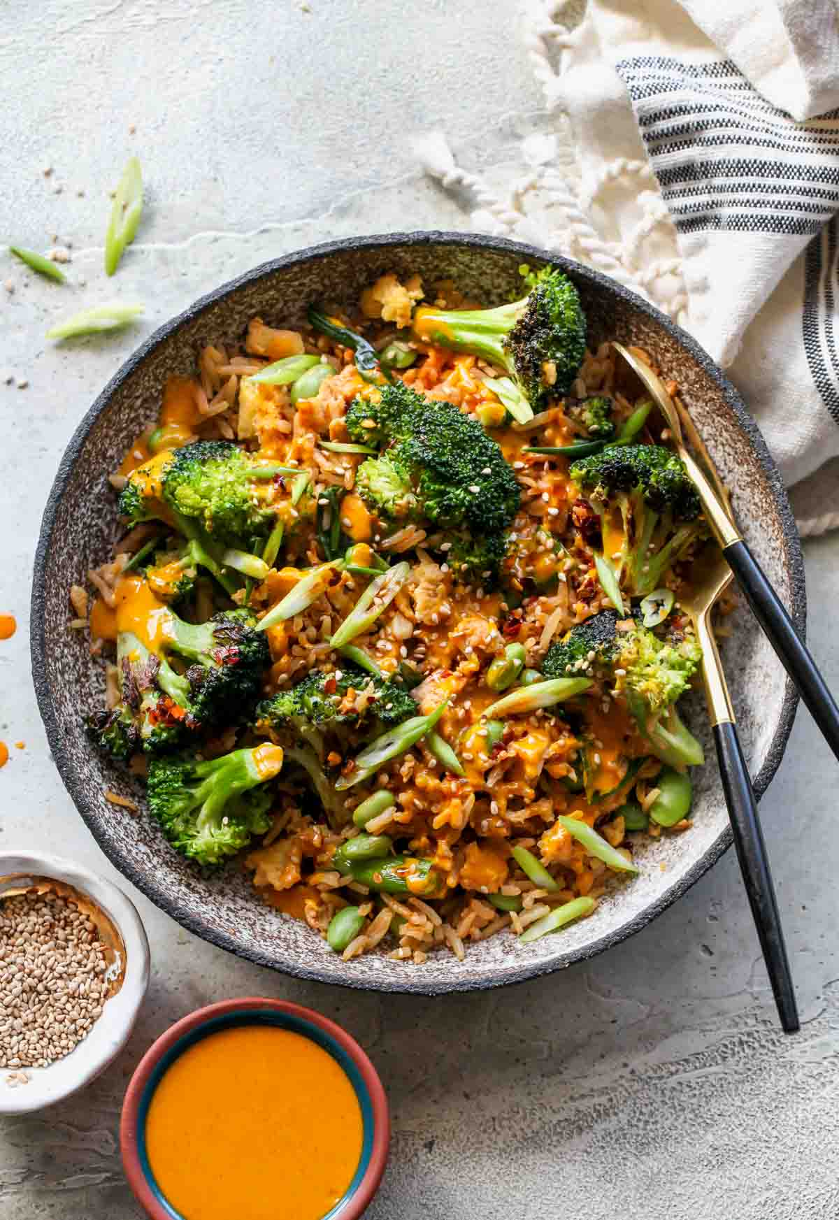 Single serving of broccoli fried rice in a bowl with serving utensils resting on the side