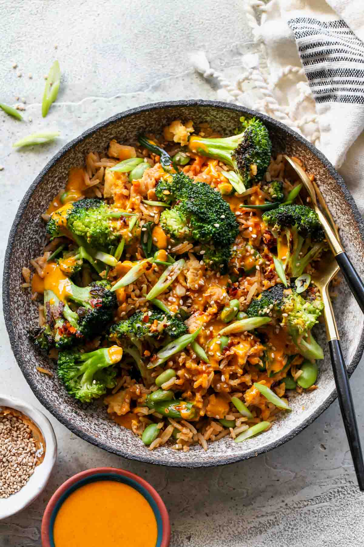 Broccoli fried rice in a grey bowl with sauce drizzled overtop