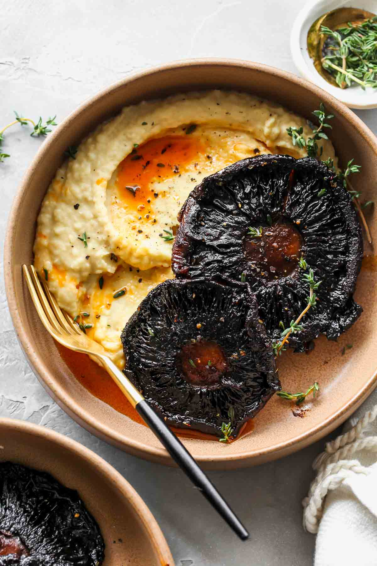 Butter bean mash in a tan bowl topped with two portobello mushrooms
