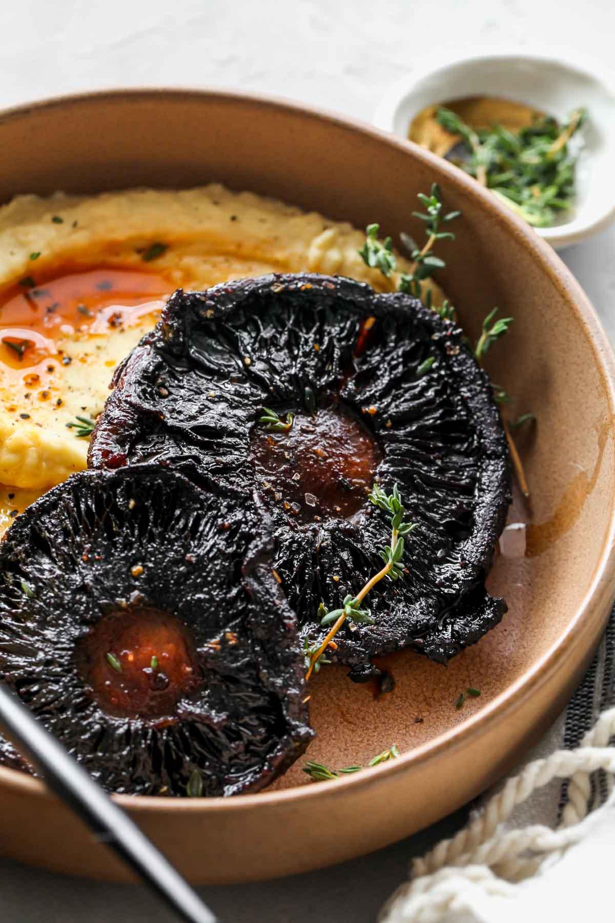 Roasted portobello mushrooms on a plate garnished with fresh tyme