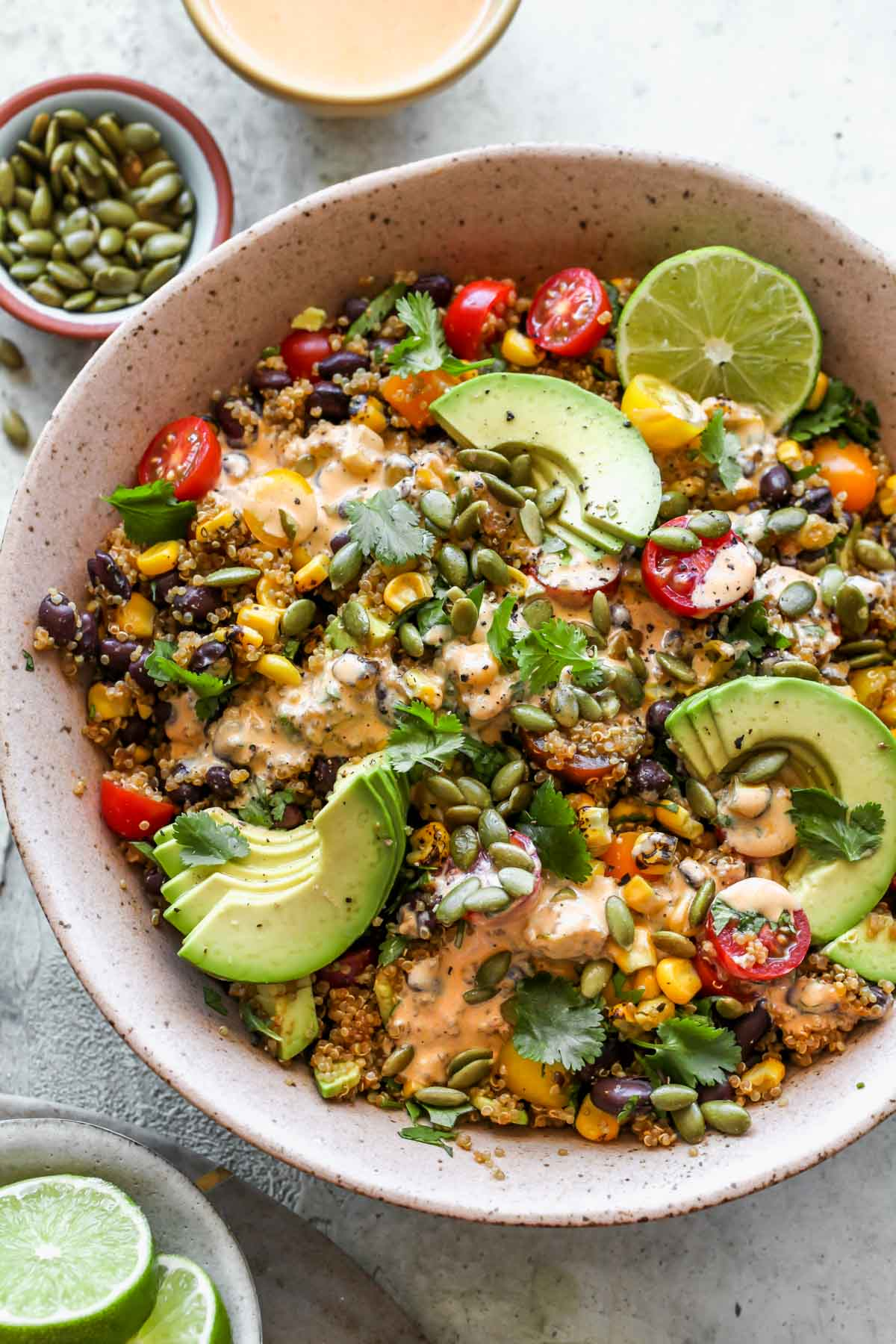 Southwest quinoa salad styled in a pink bowl topped with avocado slices