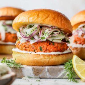Salmon burger in a brioche bun layered with yogurt spread and fennel slaw