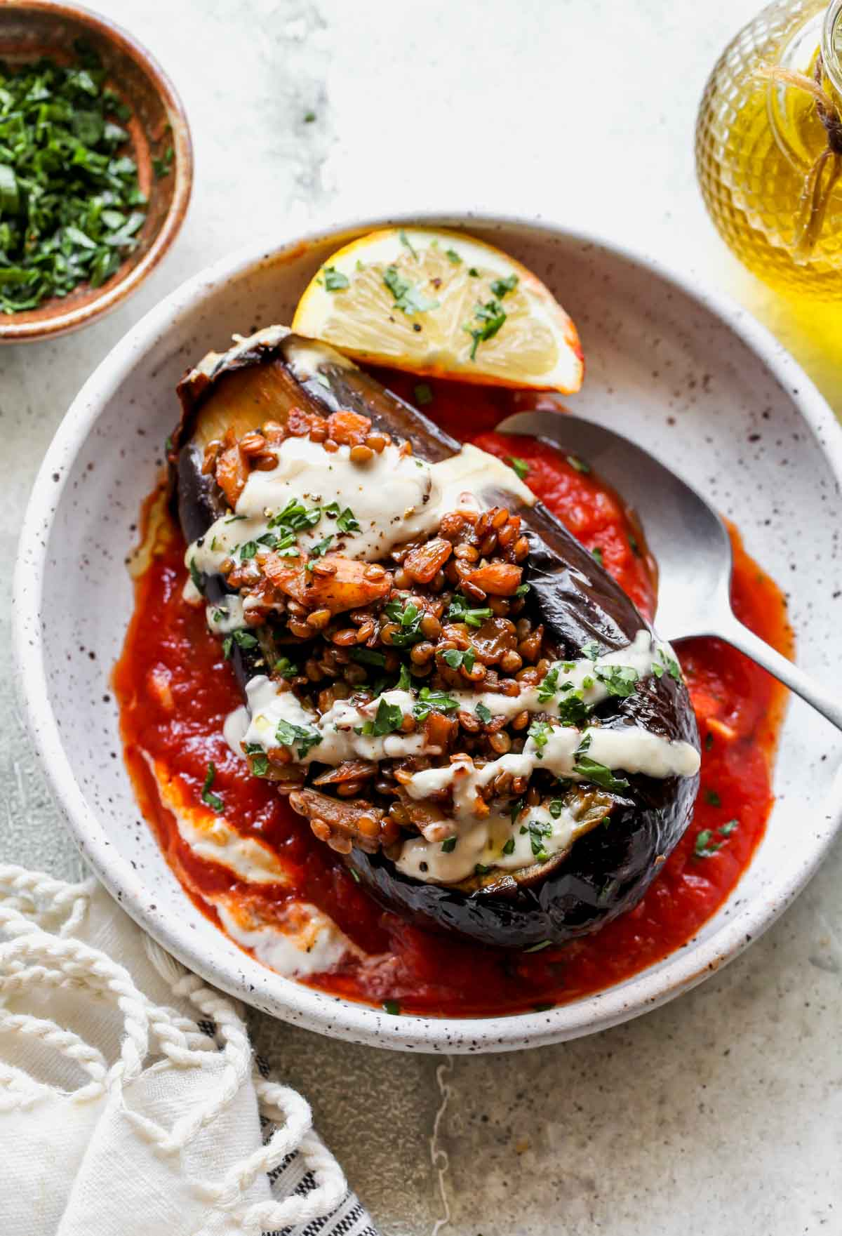 One filled eggplant in a white bowl topped with tahini sauce