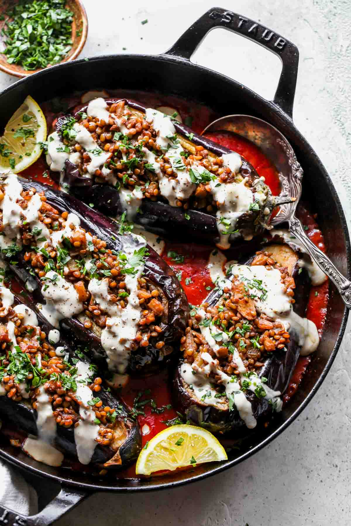 Lentil stuffed eggplants in a pan over tomato sauce