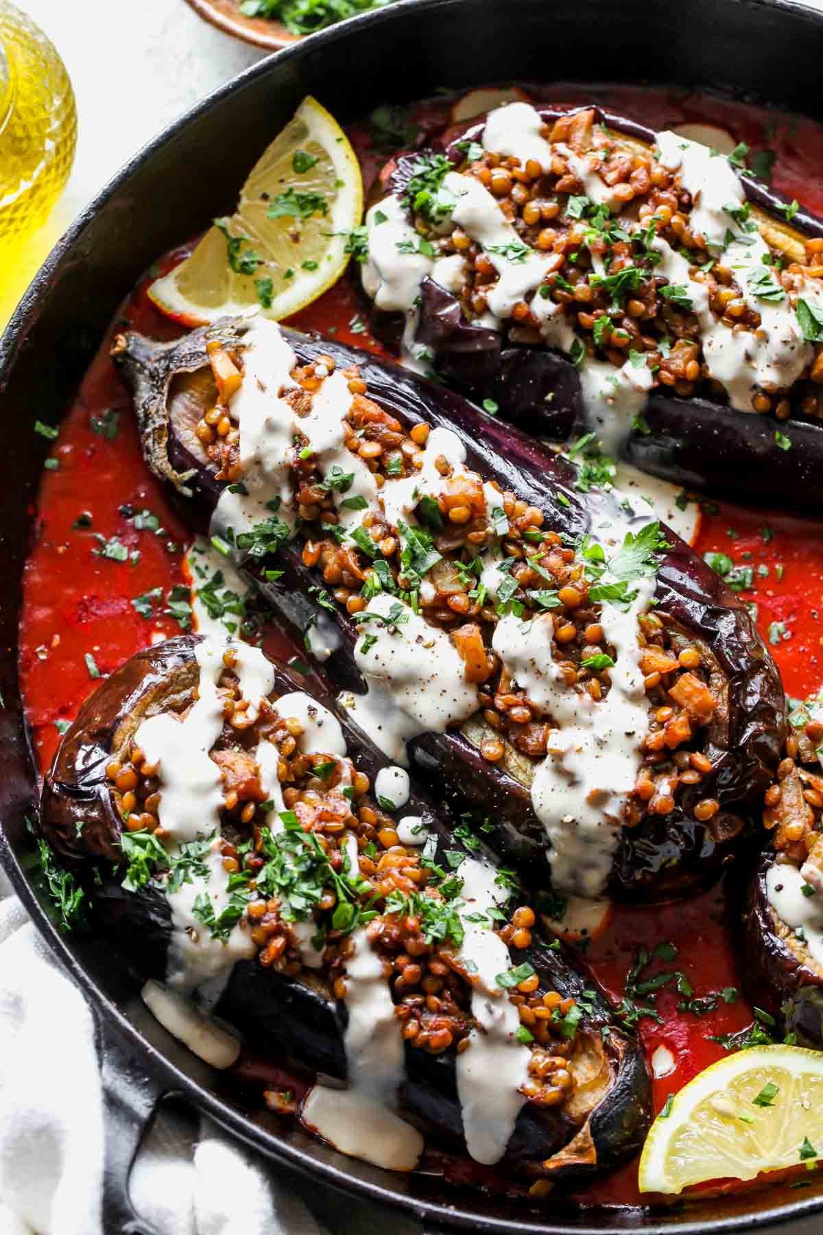Stuffed eggplants being drizzled with tahini sauce and topped with parsley