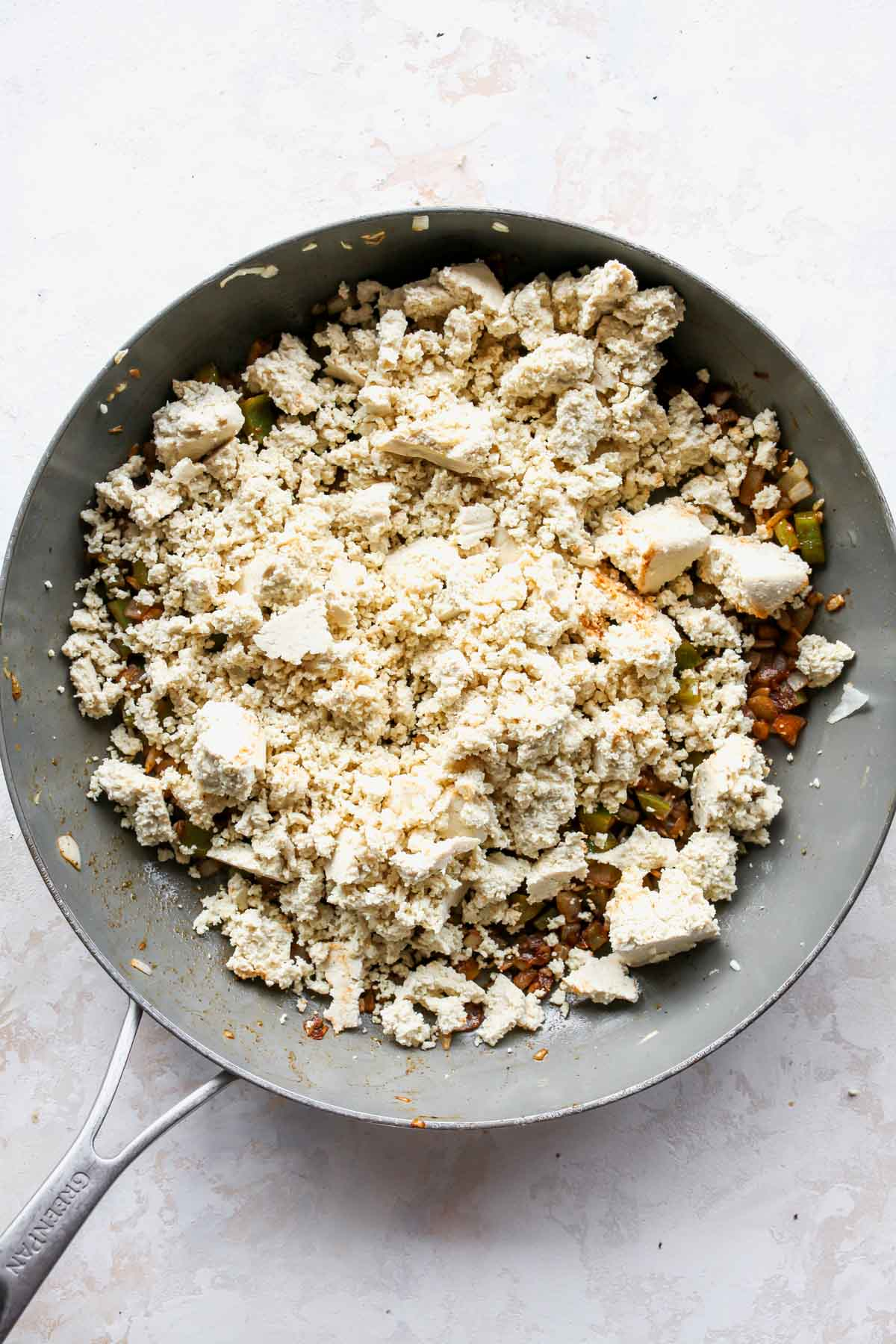 Crumbled tofu being sauteed in a large skillet