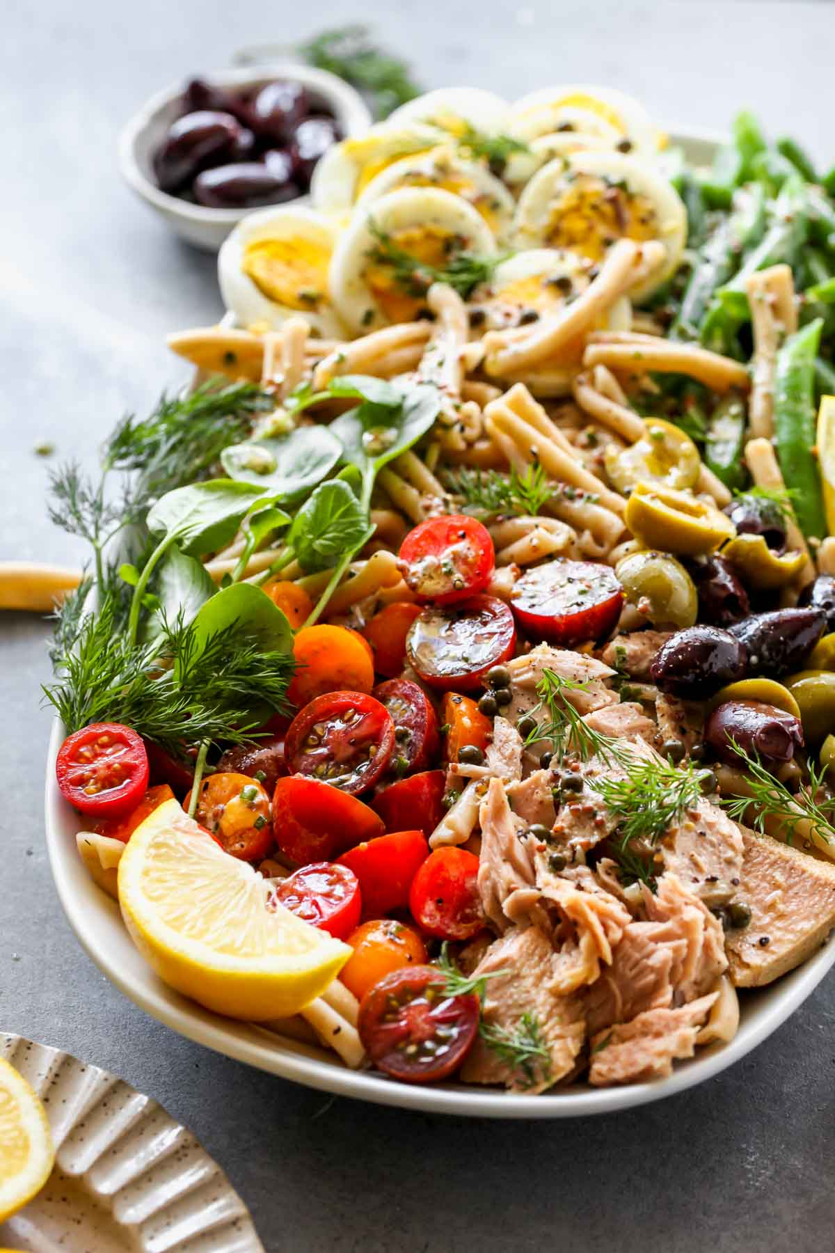 Tuna pasta salad on a platter with tomatoes, eggs, and green beans