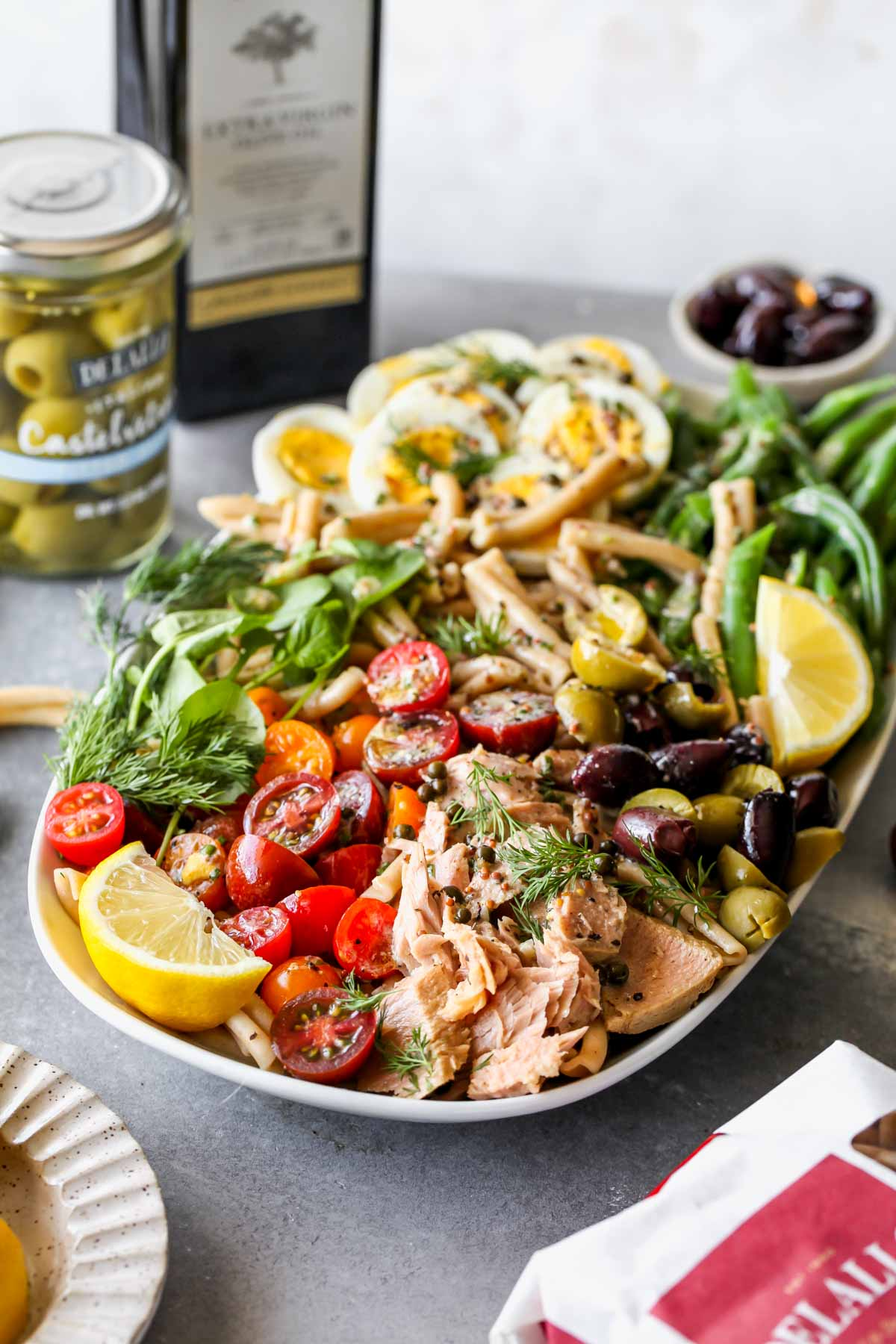 Niçoise Pasta Salad with olive oil and olive jar in the background