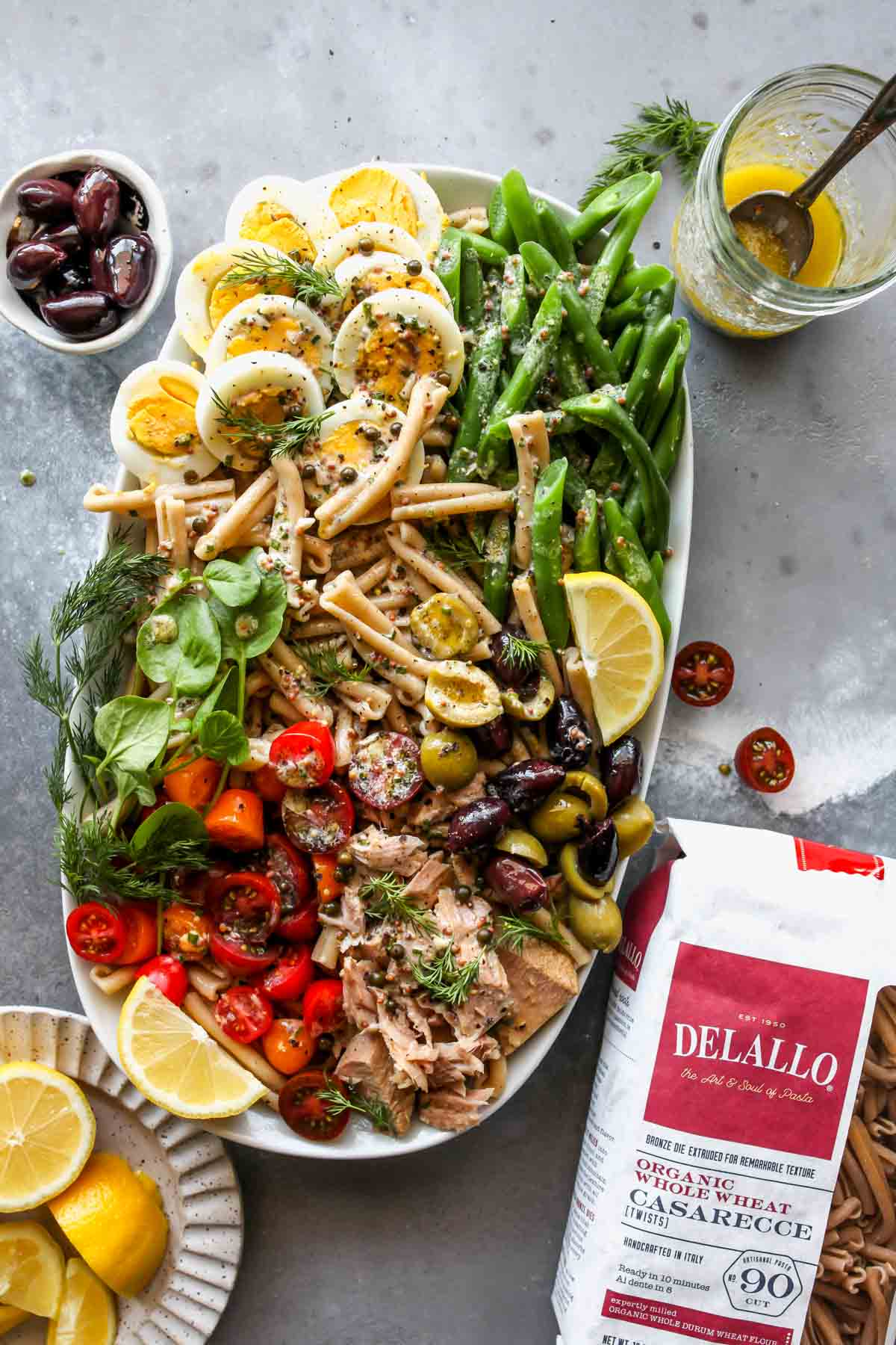 DeLallo pasta bag next to a platter of Niçoise Pasta Salad
