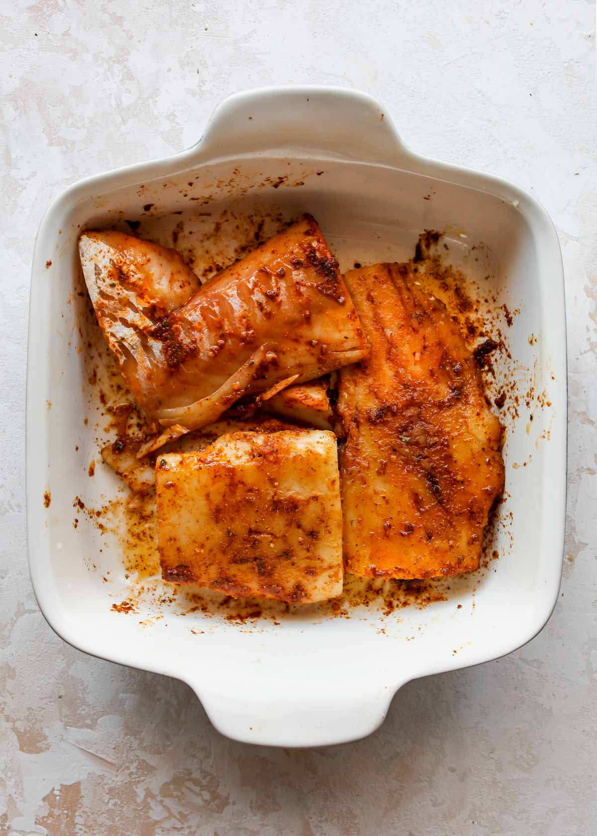 Cod marinating in a spice mixture in a dish