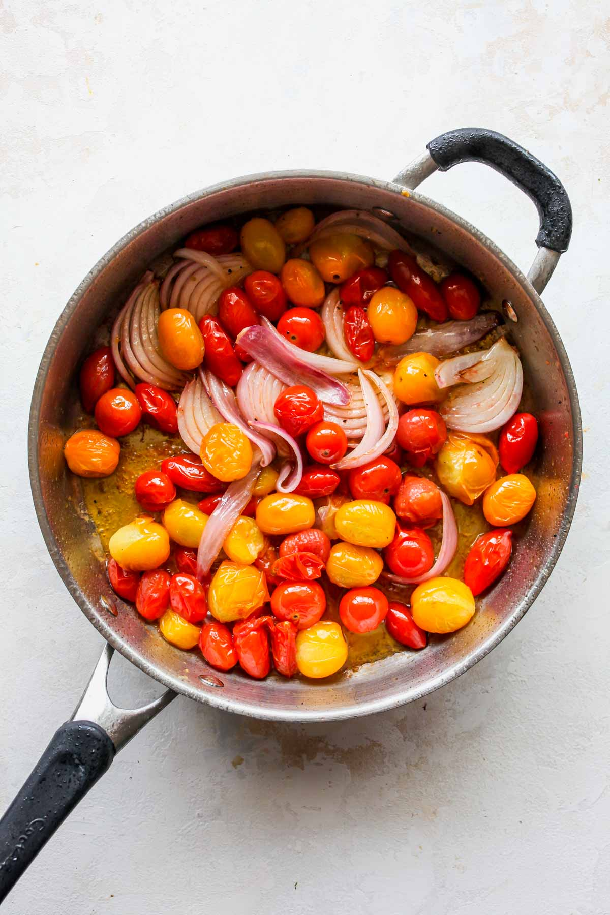 Cherry tomatoes and onions sautéing in a skillet