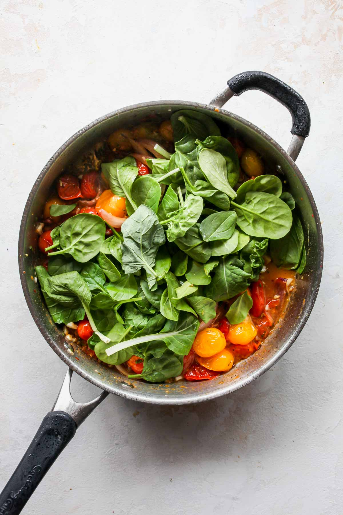 Spinach being stirred into a pan of sautéed vegetables