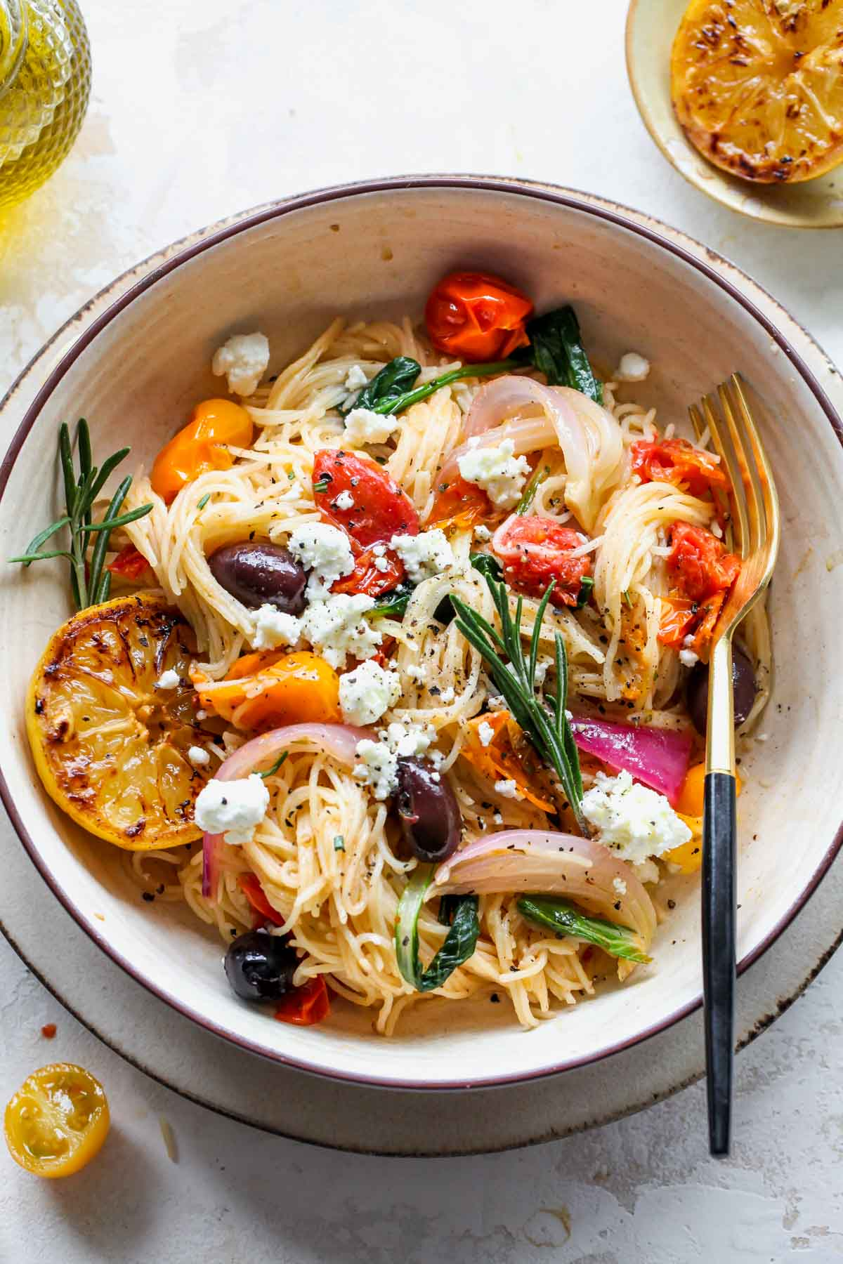 Mediterranean spaghetti in a tan bowl topped with olives and feta cheese