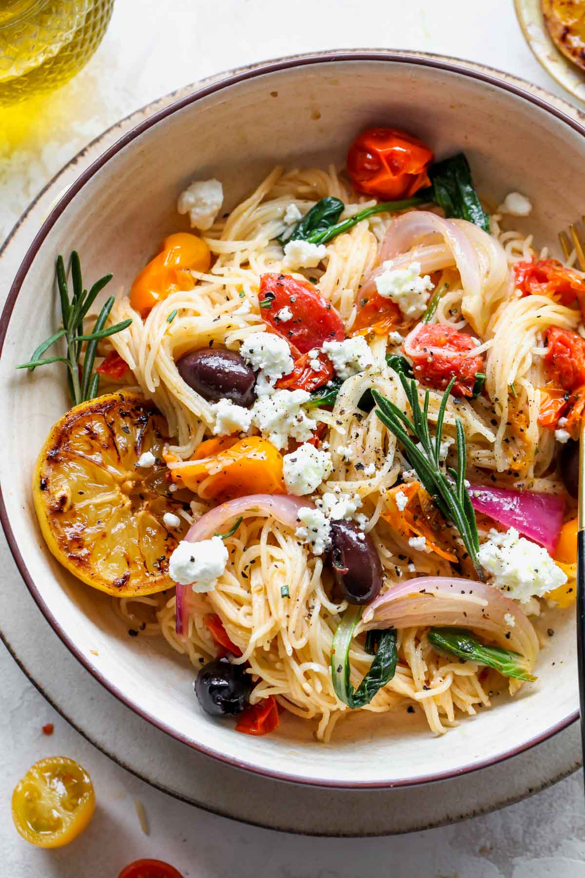 Angel hair spaghetti in a bowl with cherry tomatoes, rosemary, and olives