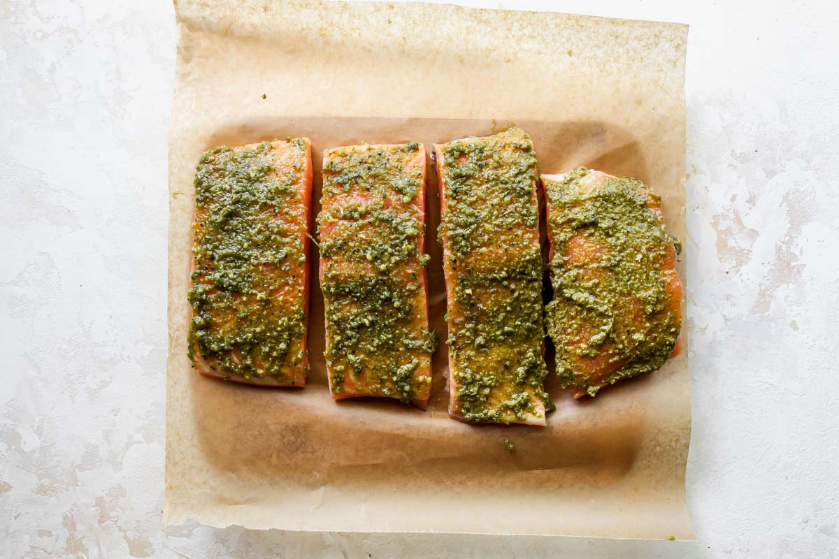 Four salmon fillets on a cutting board being rubbed with pesto