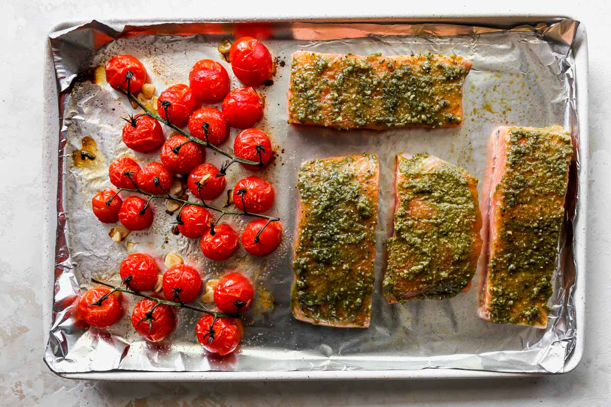 Salmon and tomatoes being roasted on rimmed baking sheet