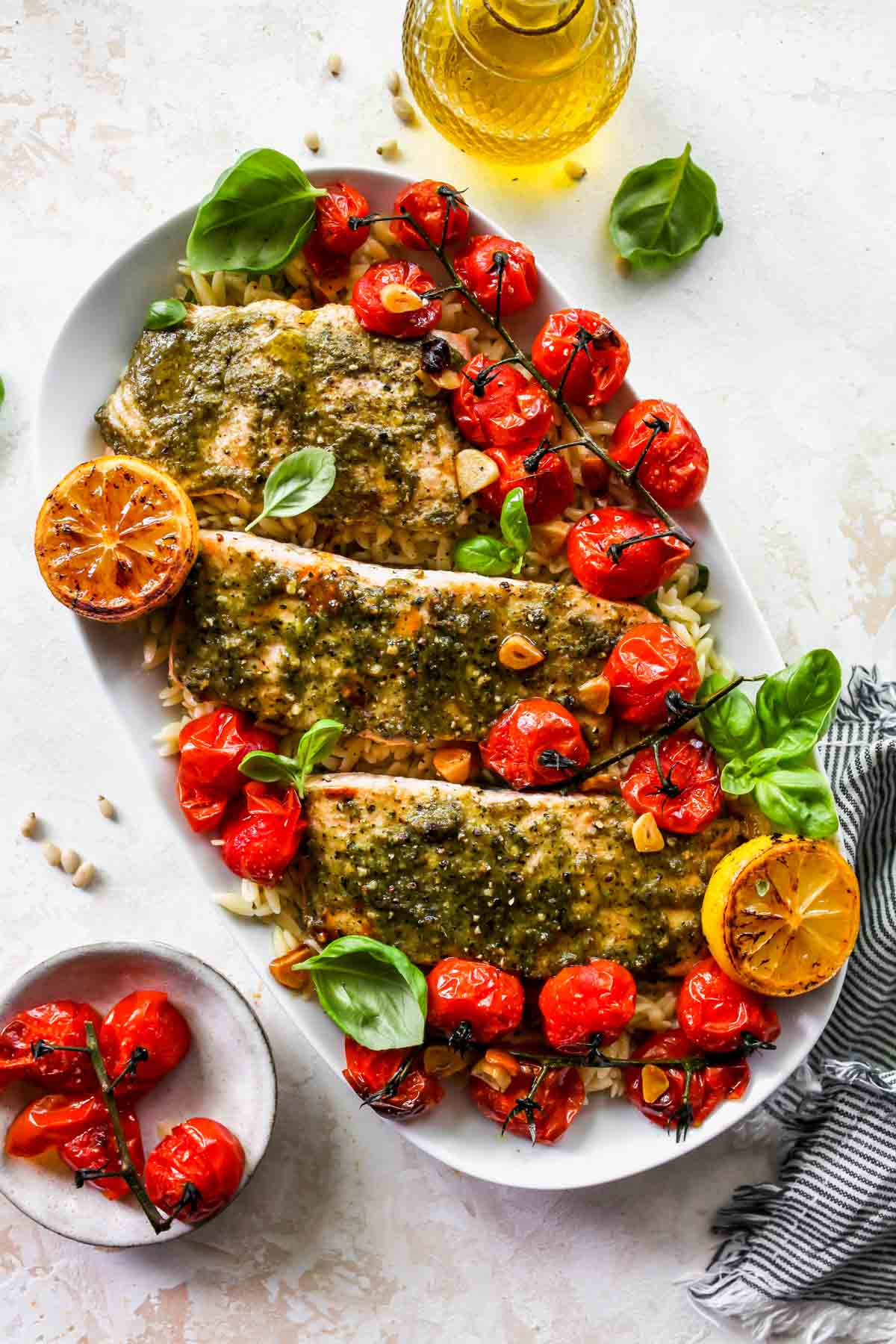 Three salmon fillets on a platter over orzo with roasted tomatoes