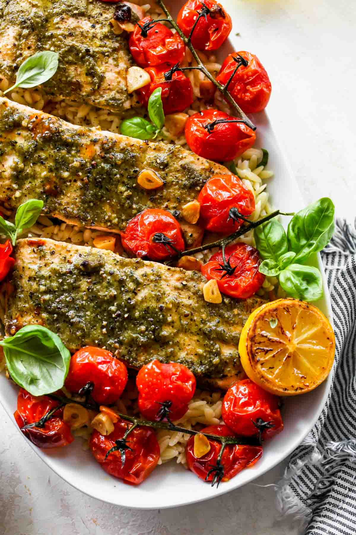 A white platter filled with roasted tomato orzo topped with pesto salmon and lemon