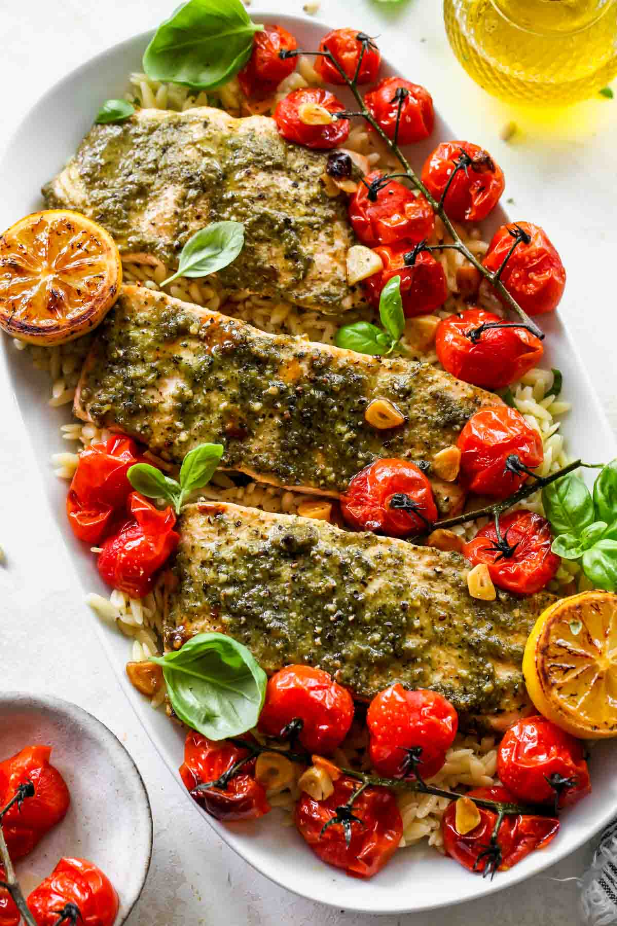 A platter of roasted tomato orzo topped with pesto salmon