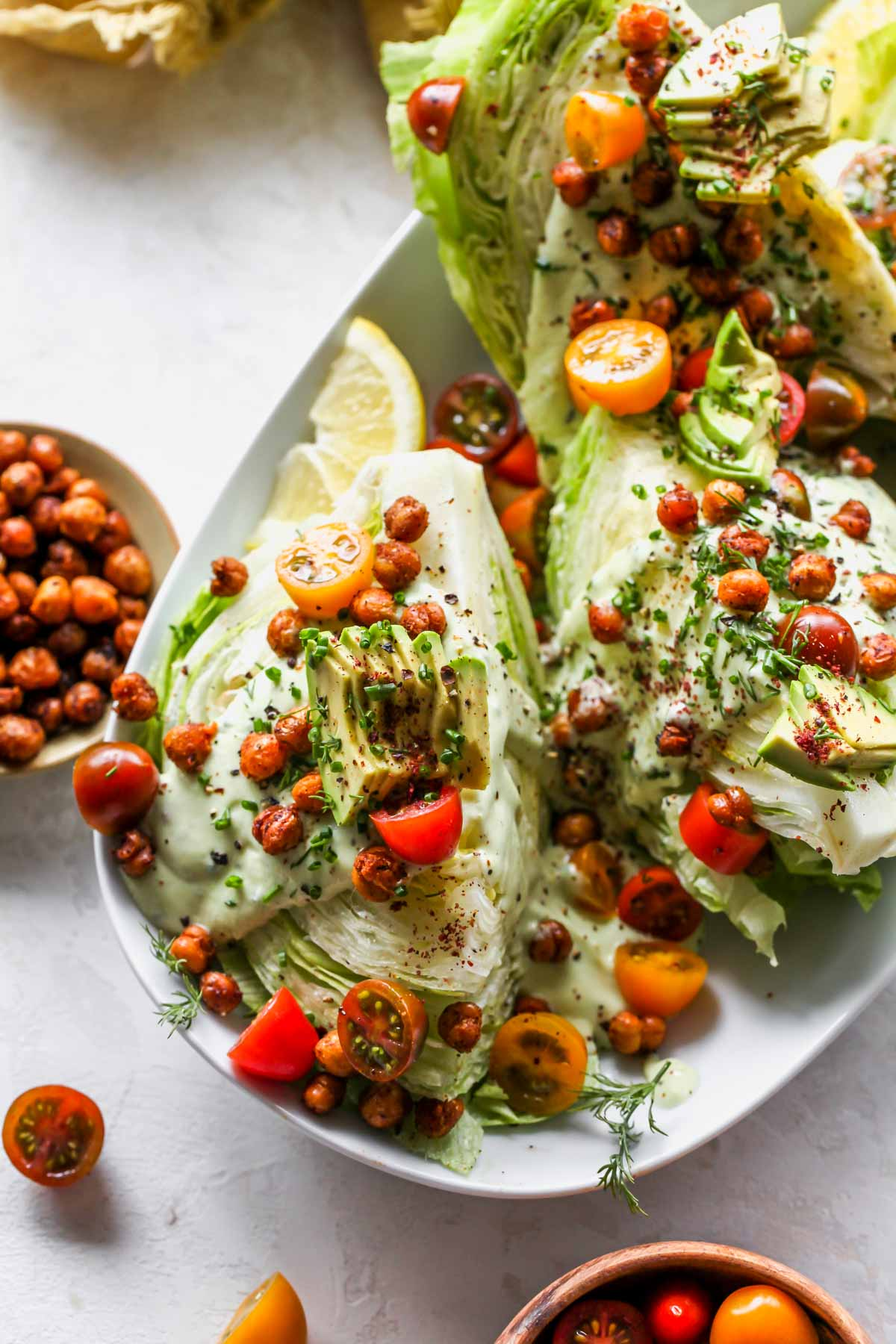Wedge salad on a platter topped with tomatoes, avocado, and herbs