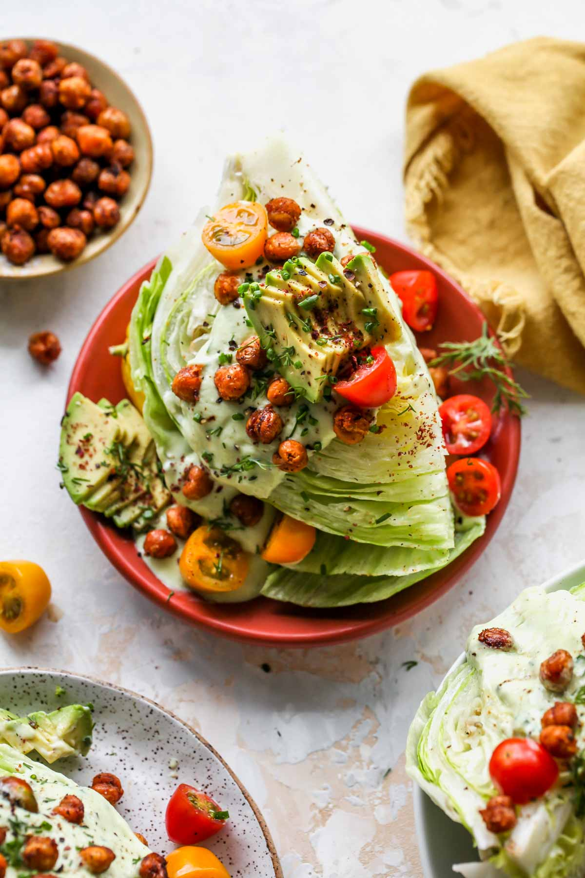 Iceberg salads on separate plates topped with dressing, chickpeas, tomatoes and herbs