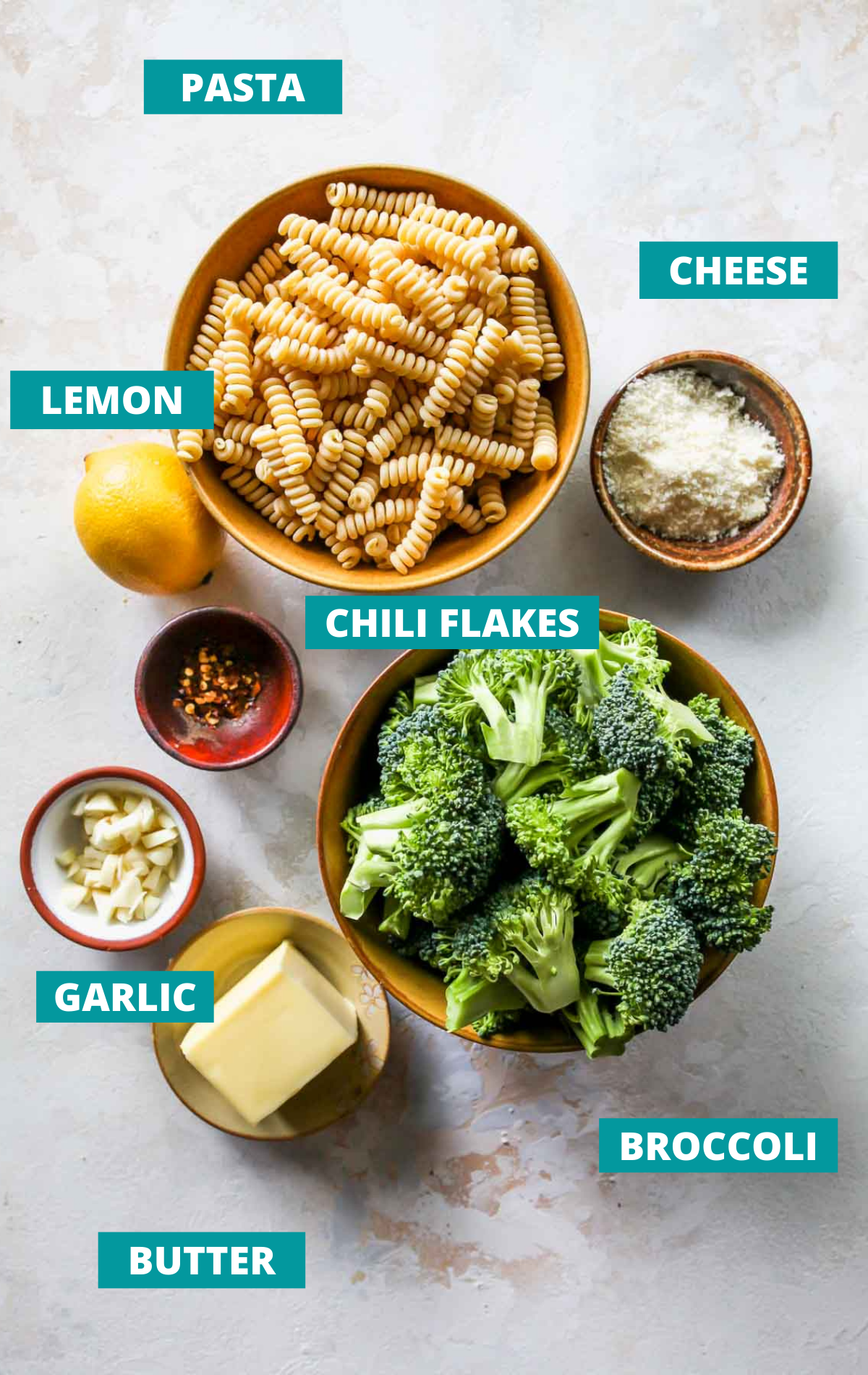 Broccoli pasta ingredients in separate bowls on a white board
