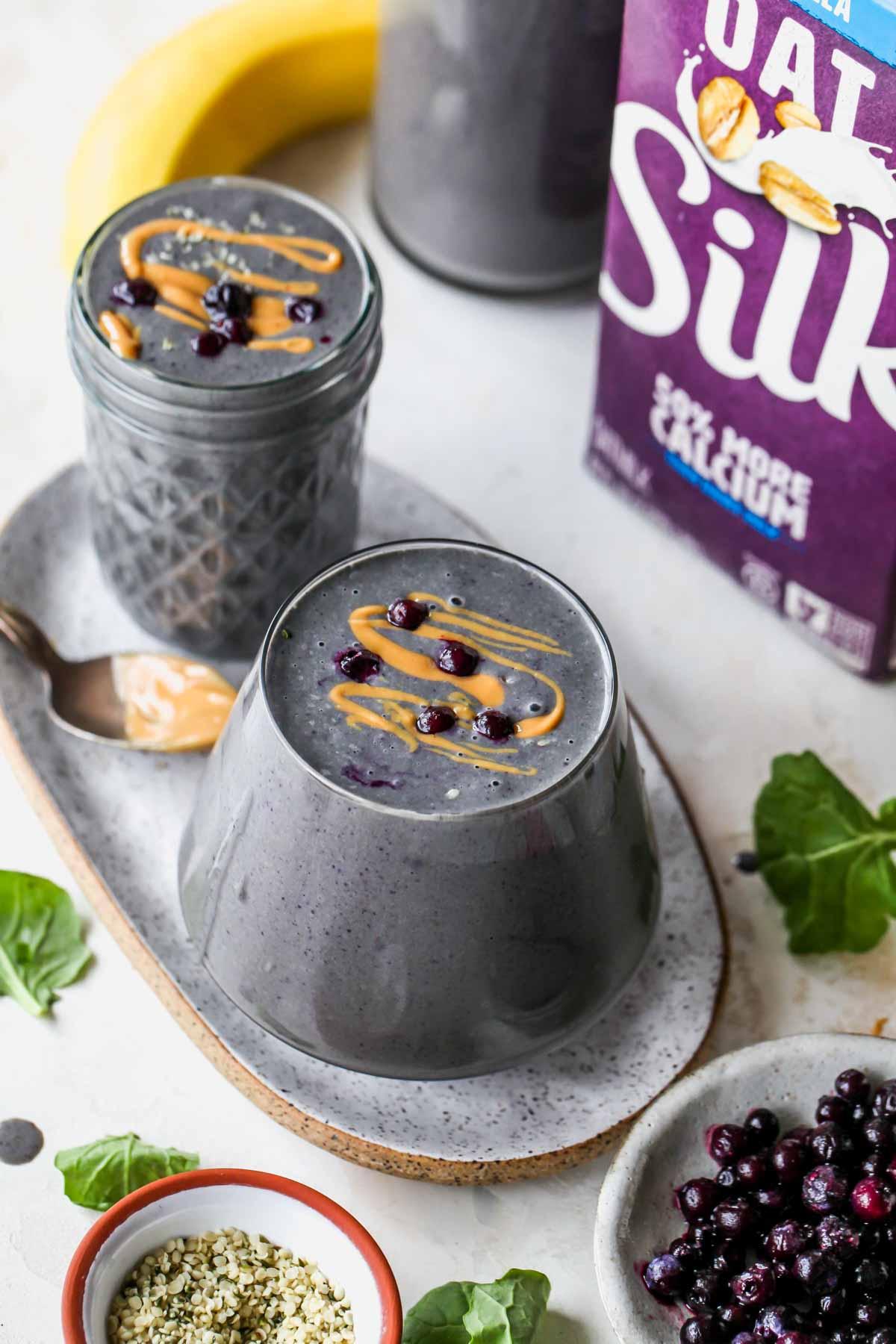 Silk Oatmilk carton next to a berry smoothie