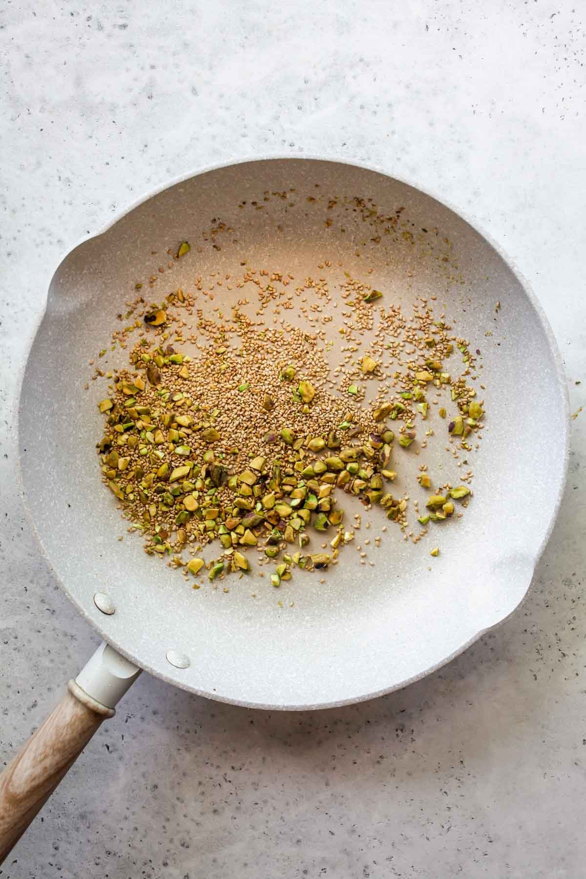 Pistachios and sesame seeds being toasted in a skillet