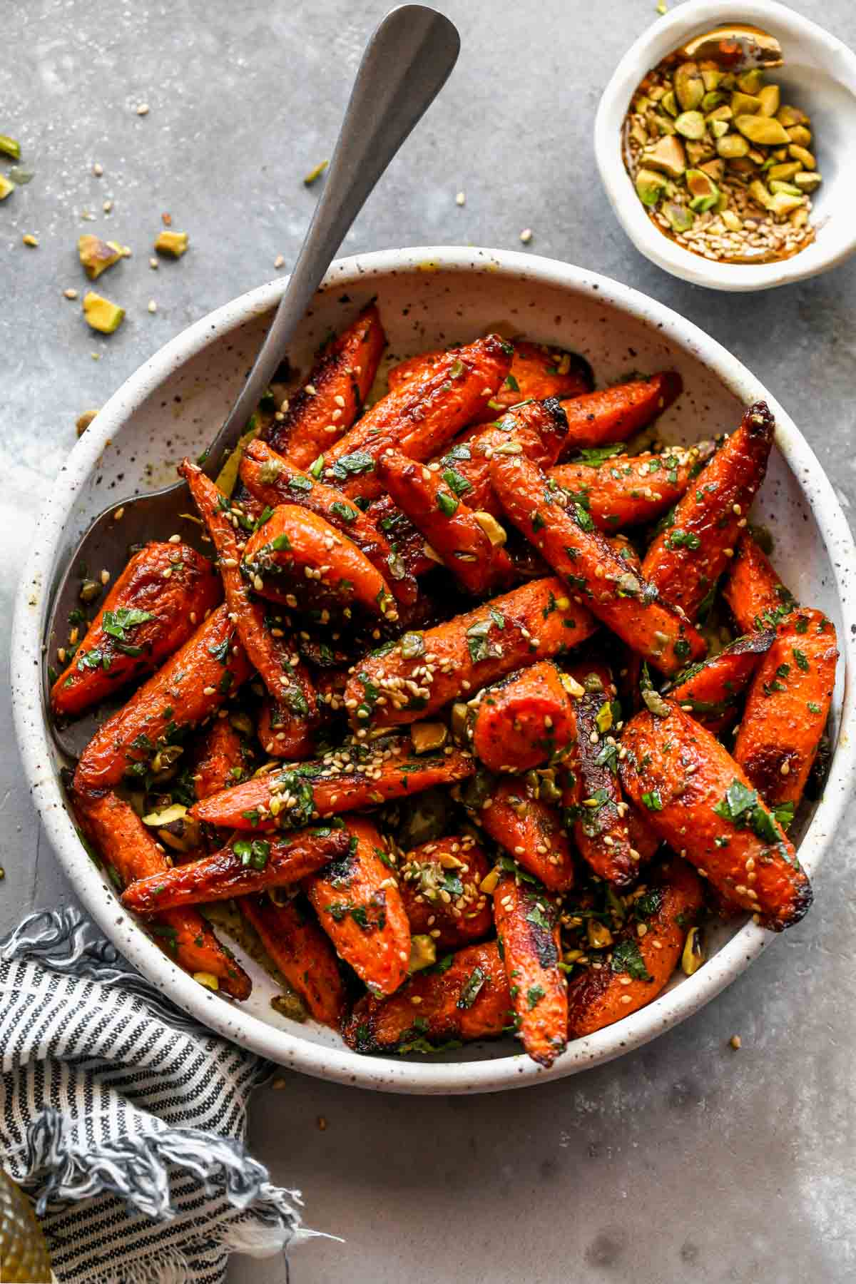 Roasted carrots in a white bowl topped with parsley and pistachios