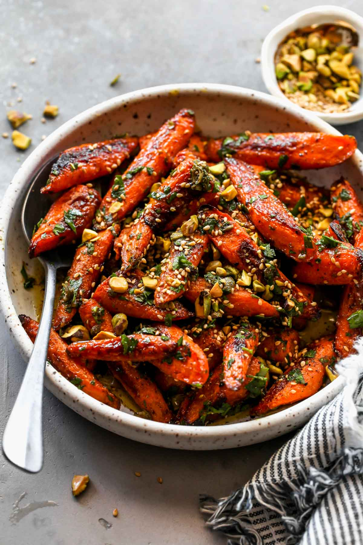 Spice roasted carrots topped with nuts and seeds in a white bowl