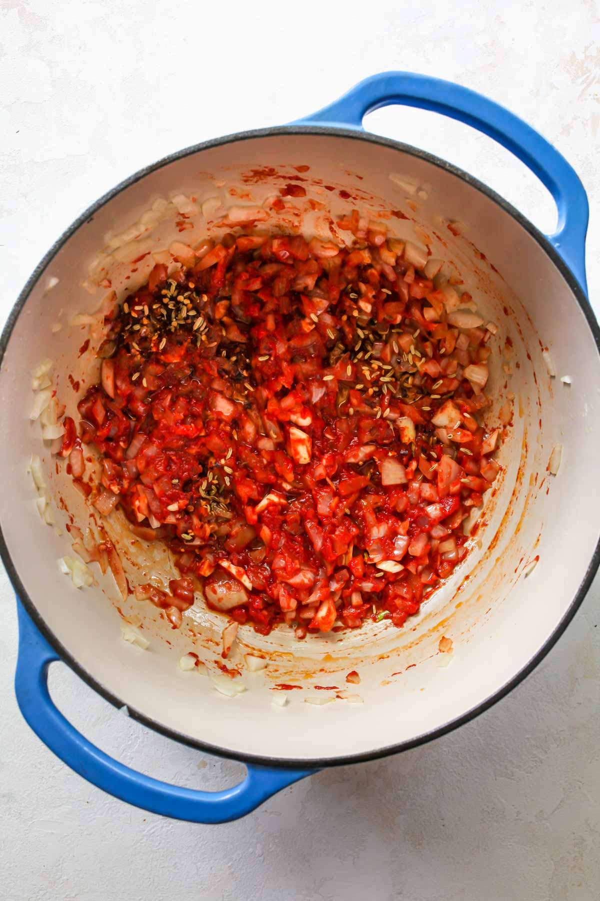 Onions, garlic, and tomato paste being simmered in a pot