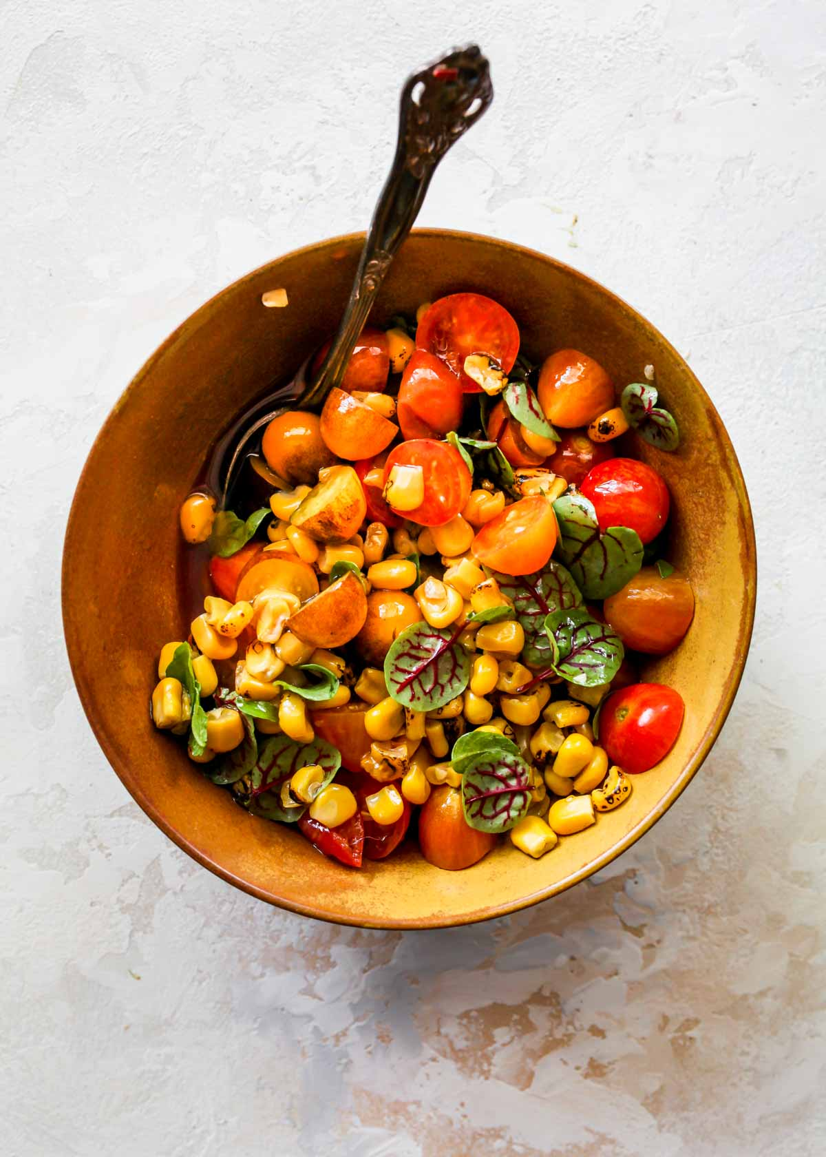 Cherry tomatoes, corn, basil, vinegar, and olive oil being stirred in a bowl
