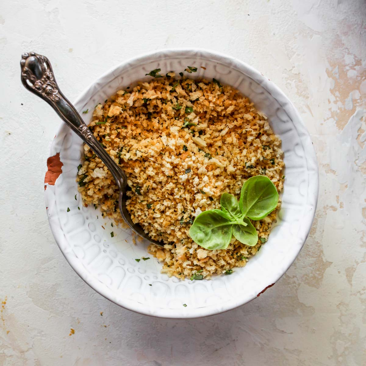 Toasted breadcrumbs and pine nuts in a bowl with fresh basil