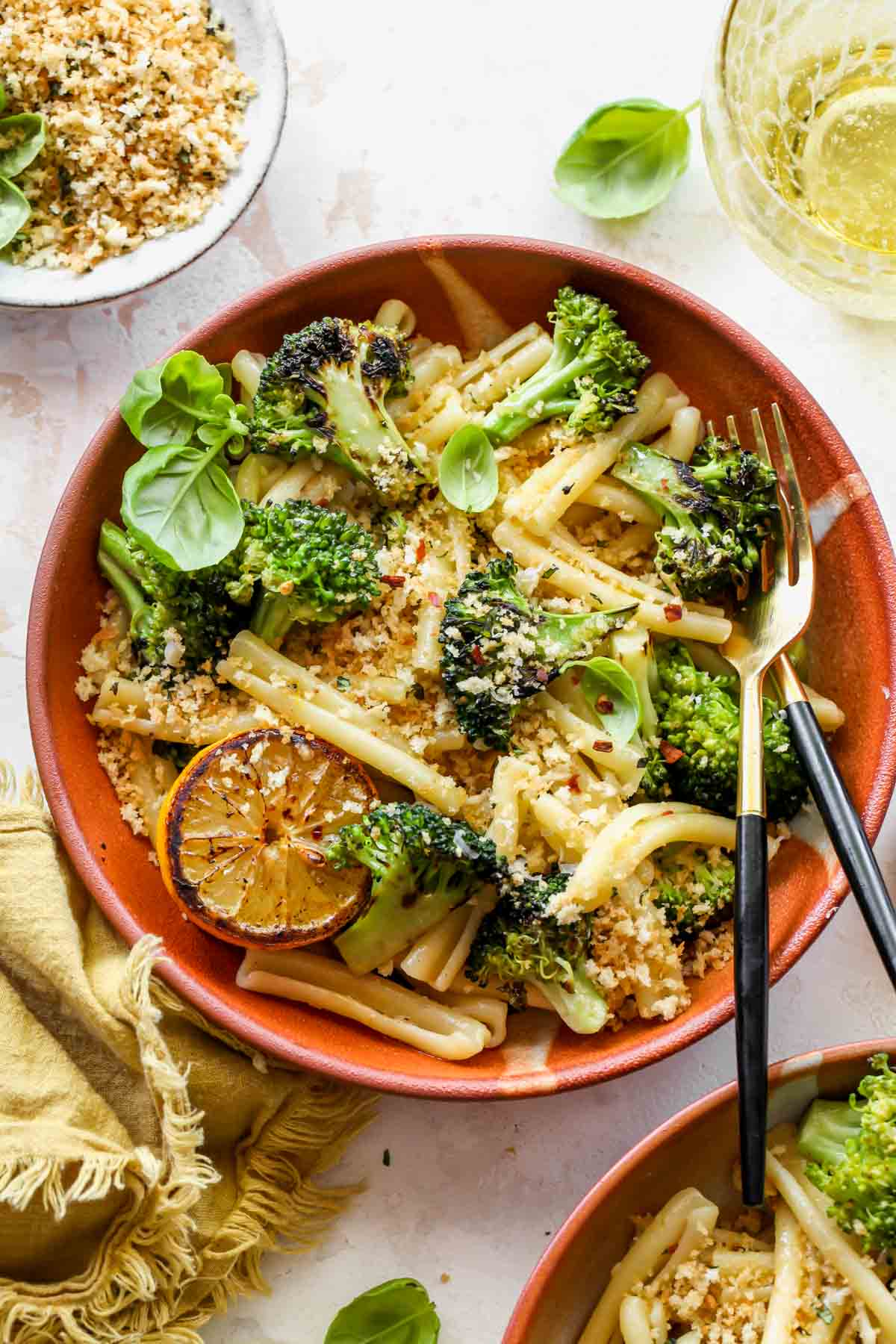 Broccoli pasta in an orange bowl topped with basil breadcrumbs and lemon slice