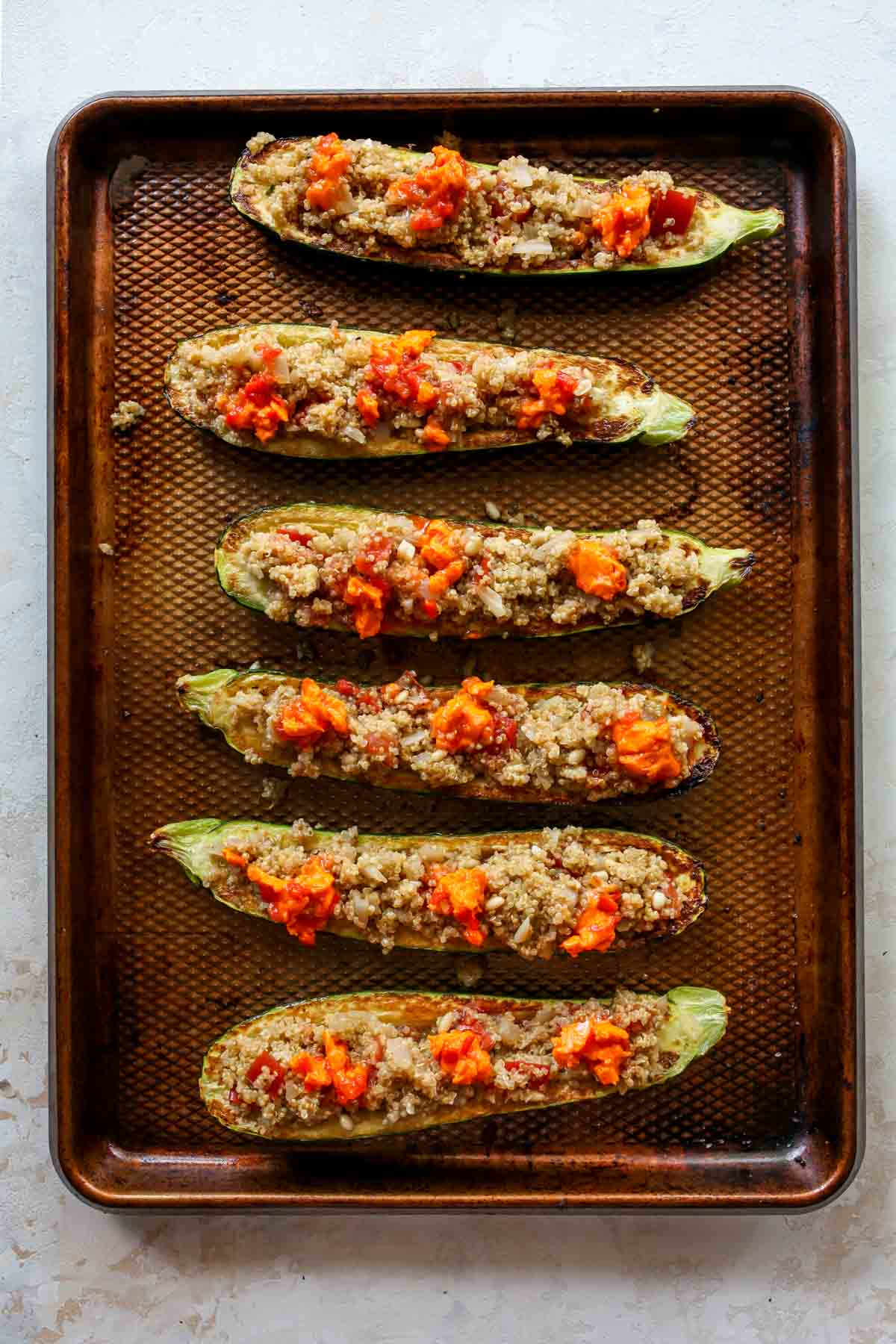 Zucchini boats being stuffed with quinoa mixture before baking