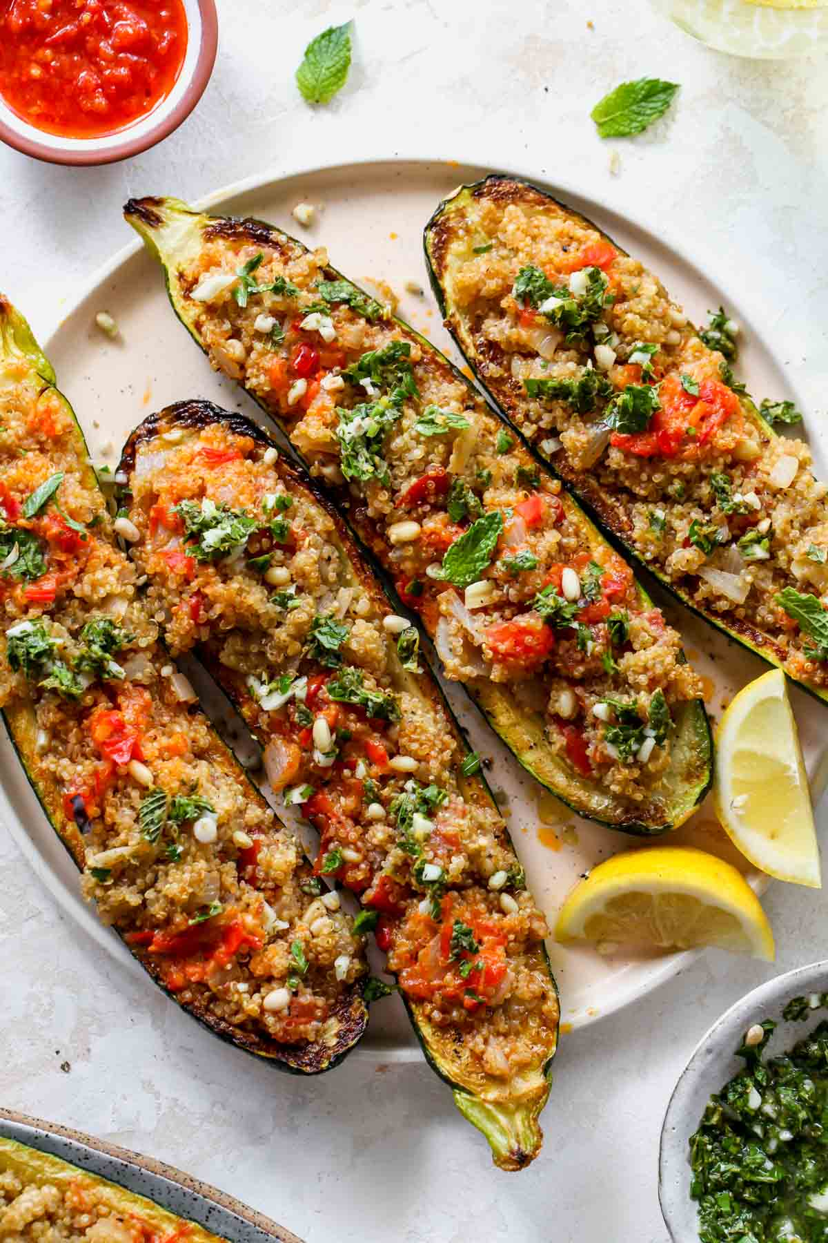 Zucchini boats filled with quinoa on a plate with lemon wedges