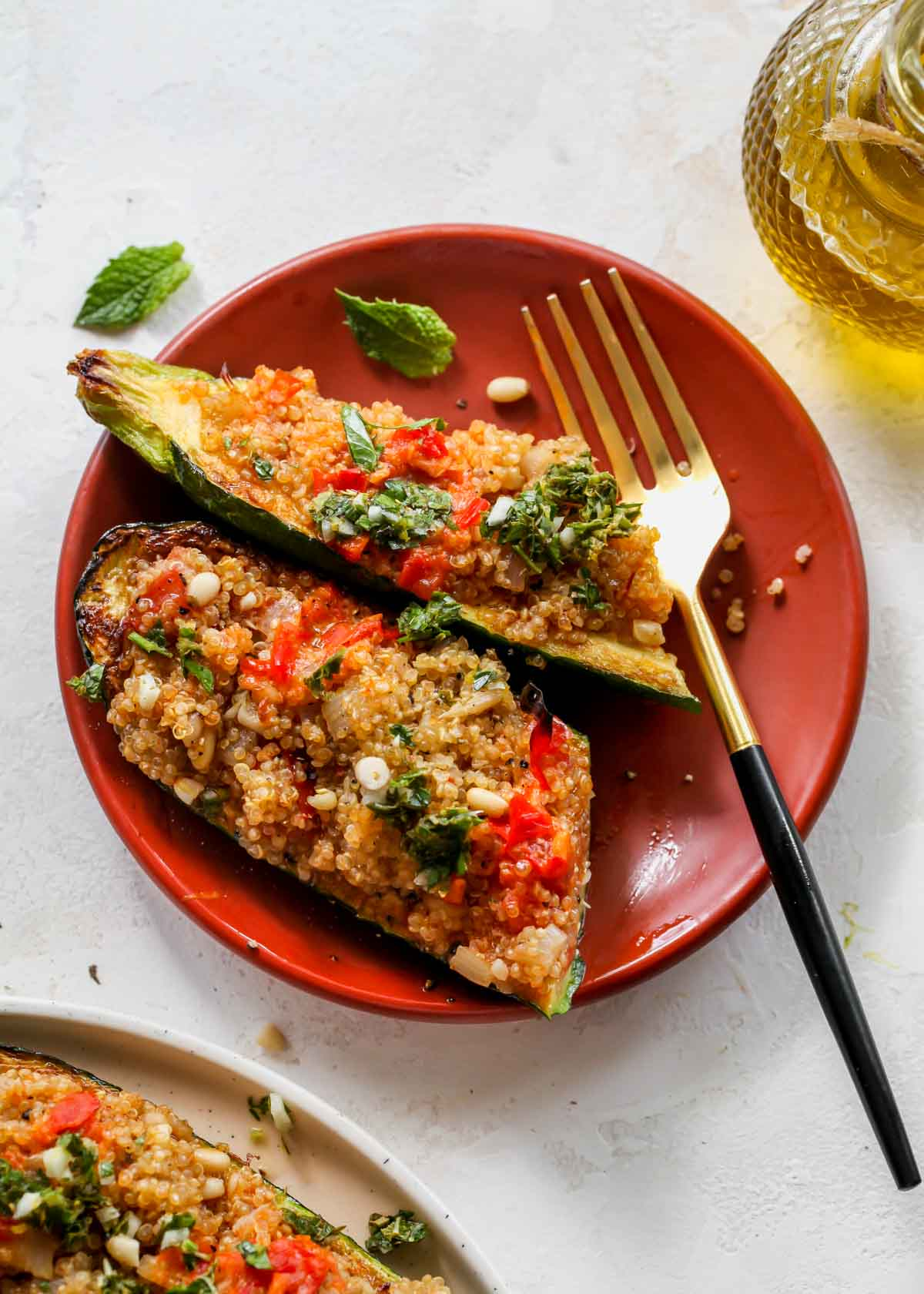A stuffed zucchini being sliced in half on a plate