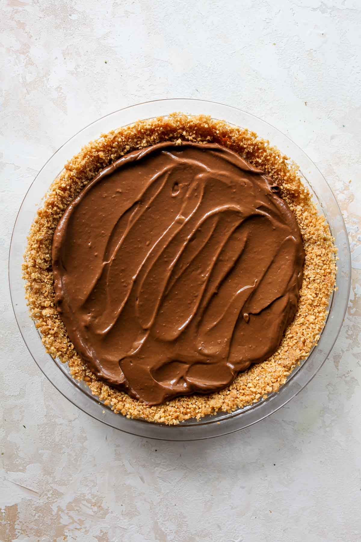 Chocolate pudding being spread in a pie crust