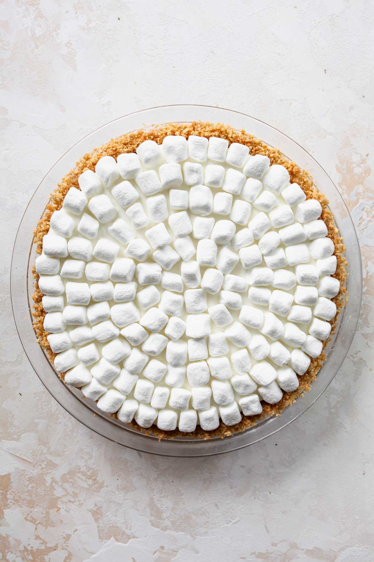 Mini marshmallows being placed on top of a pie