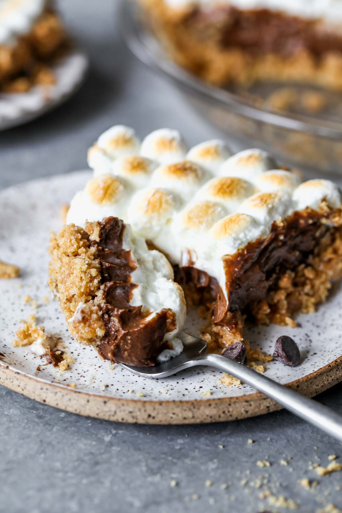 S'mores pie on a plate with a fork taking a bite out
