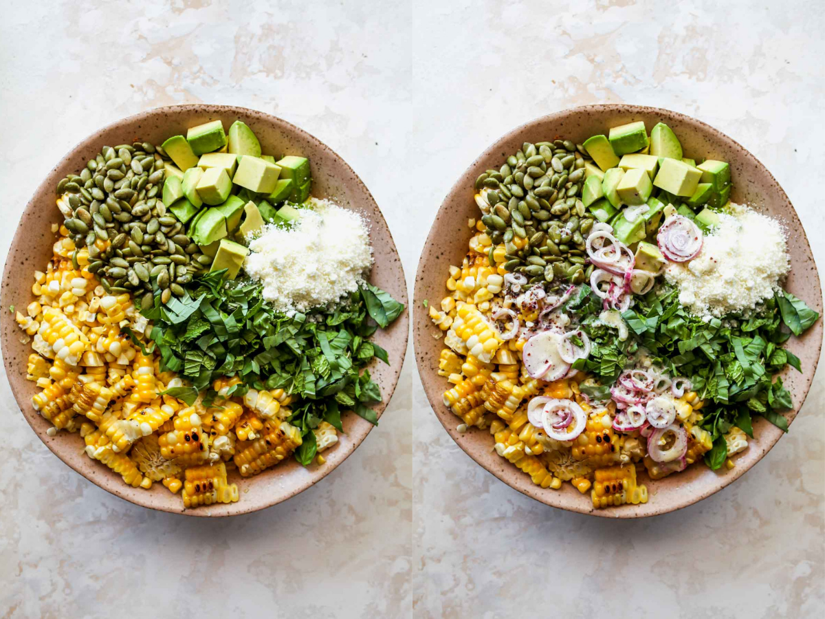 Corn, herbs, avocado, and seeds being tossed with dressing in a pink bowl