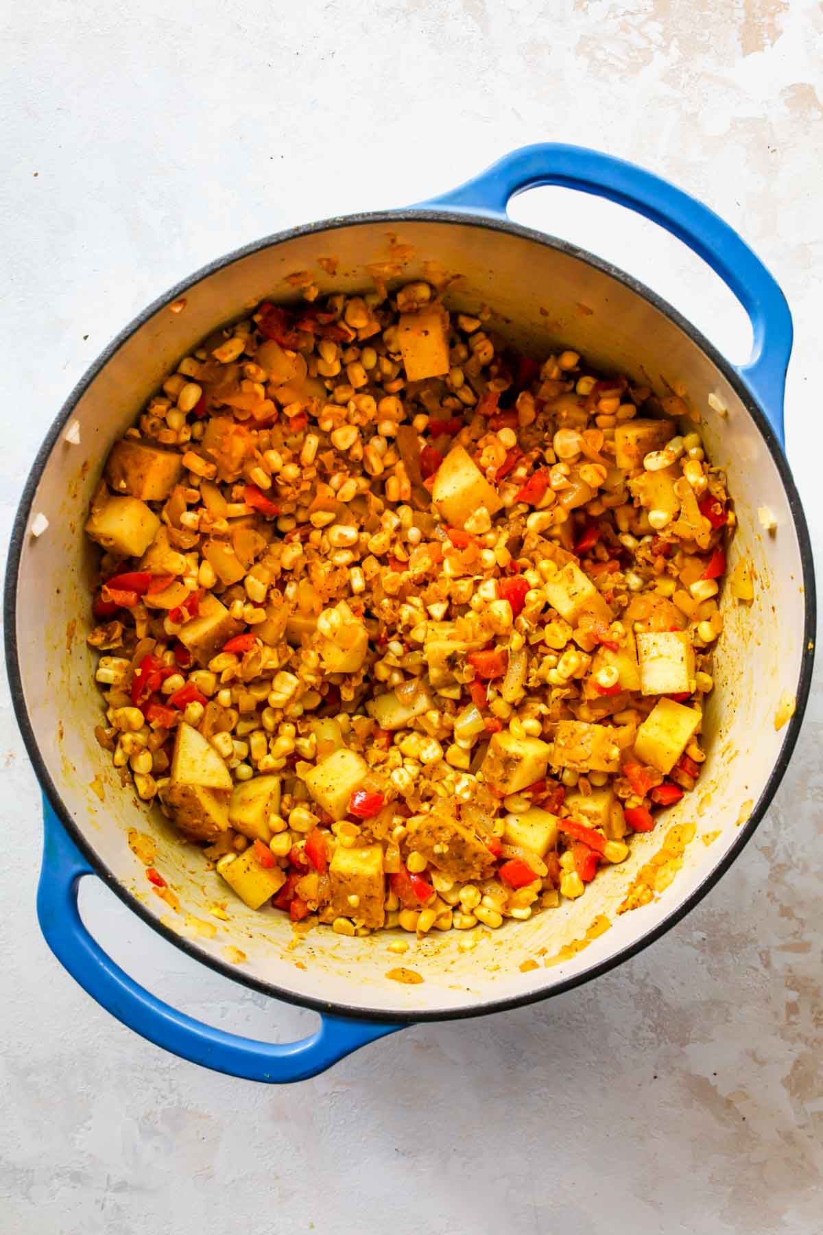 Diced potatoes and corn kernels being added to a pot